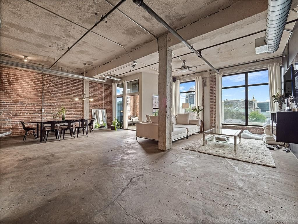 A large loft with concrete floors and brick walls.