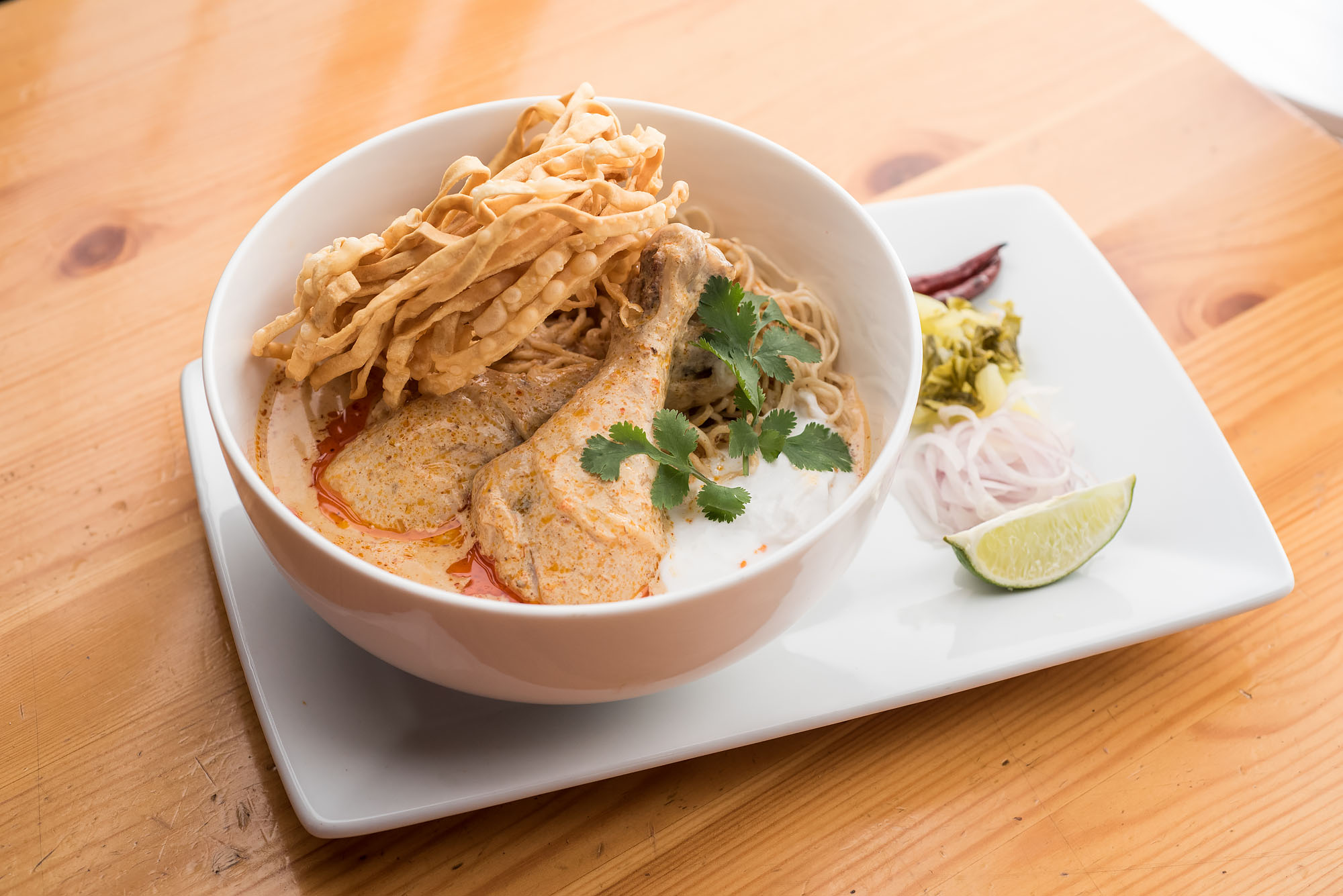 Khao soi at Ayara Thai, presented in a white bowl with lime wedge on the side.