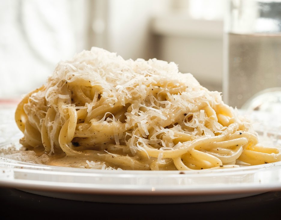a plate of piled spaghetti with grated cheese