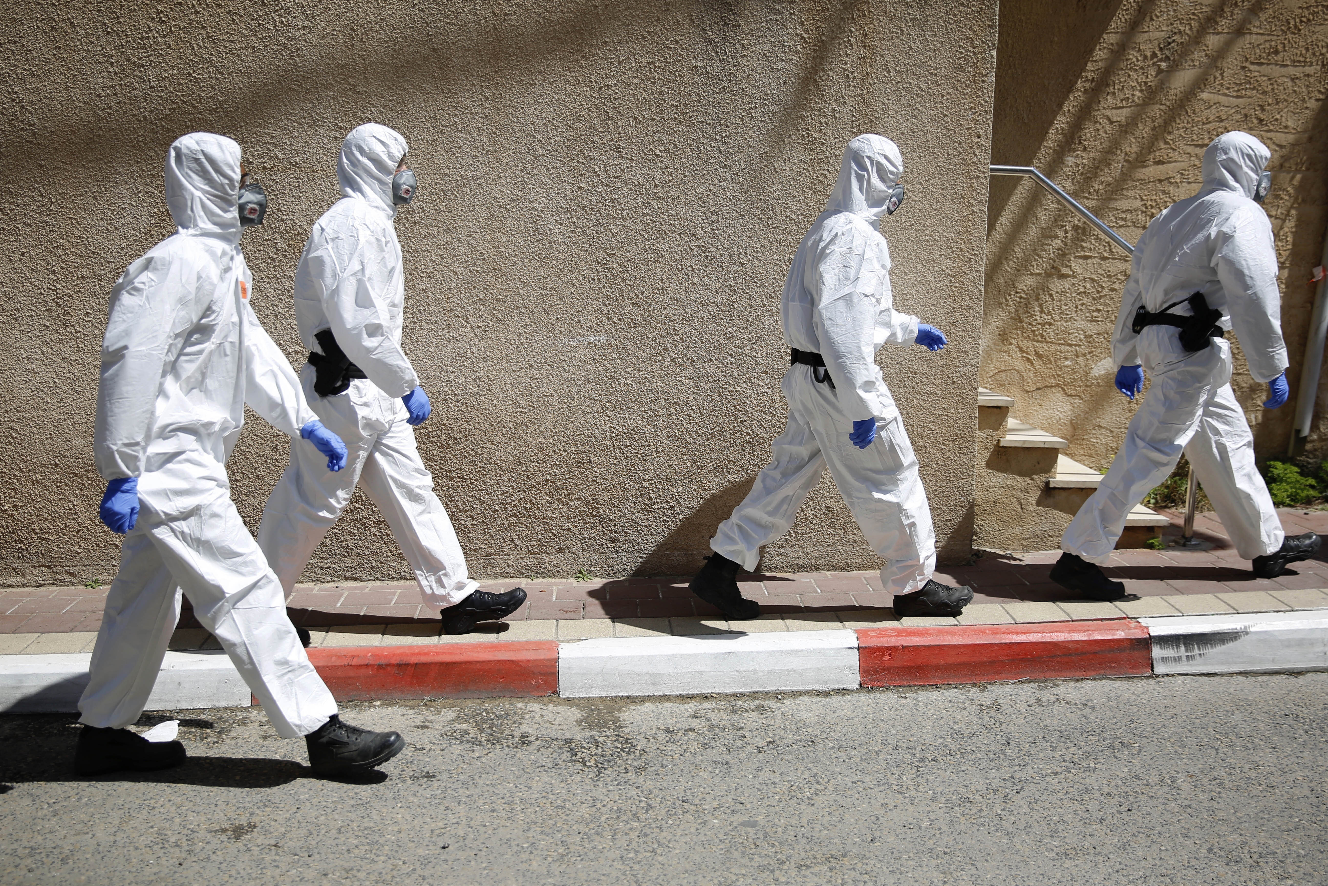 Israeli police officers wearing protective gear march toward a synagogue to detain ultra-Orthodox men because of the government's measures to help stop the spread of the coronavirus, in Bnei Brak, a suburb of Tel Aviv, Israel, Thursday, April 2, 2020.