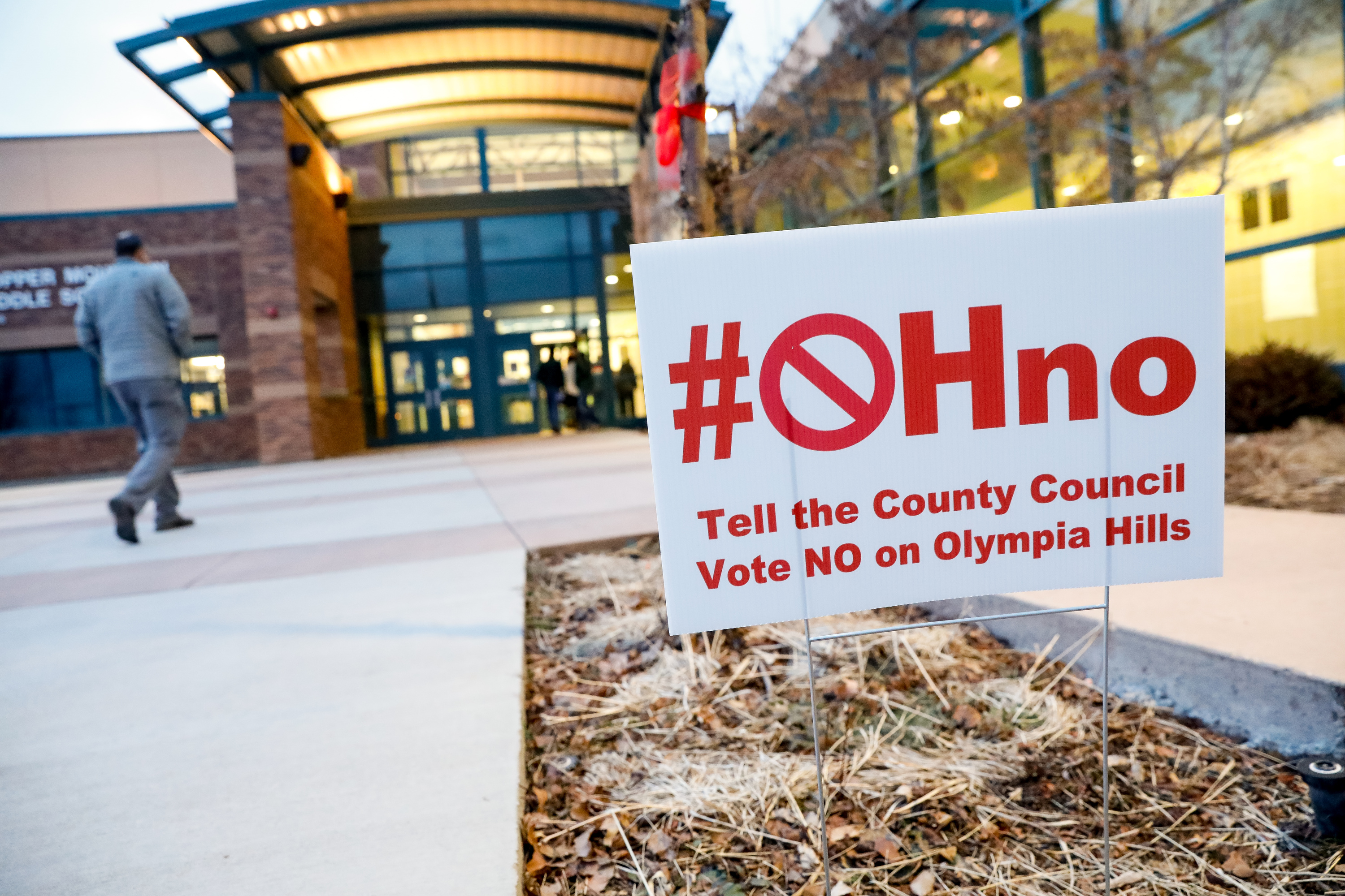 Yard signs oppose the Olympia Hills development before a public hearing with the Salt Lake County Council at Copper Mountain Middle School in Herriman on Tuesday, Jan. 28, 2020.