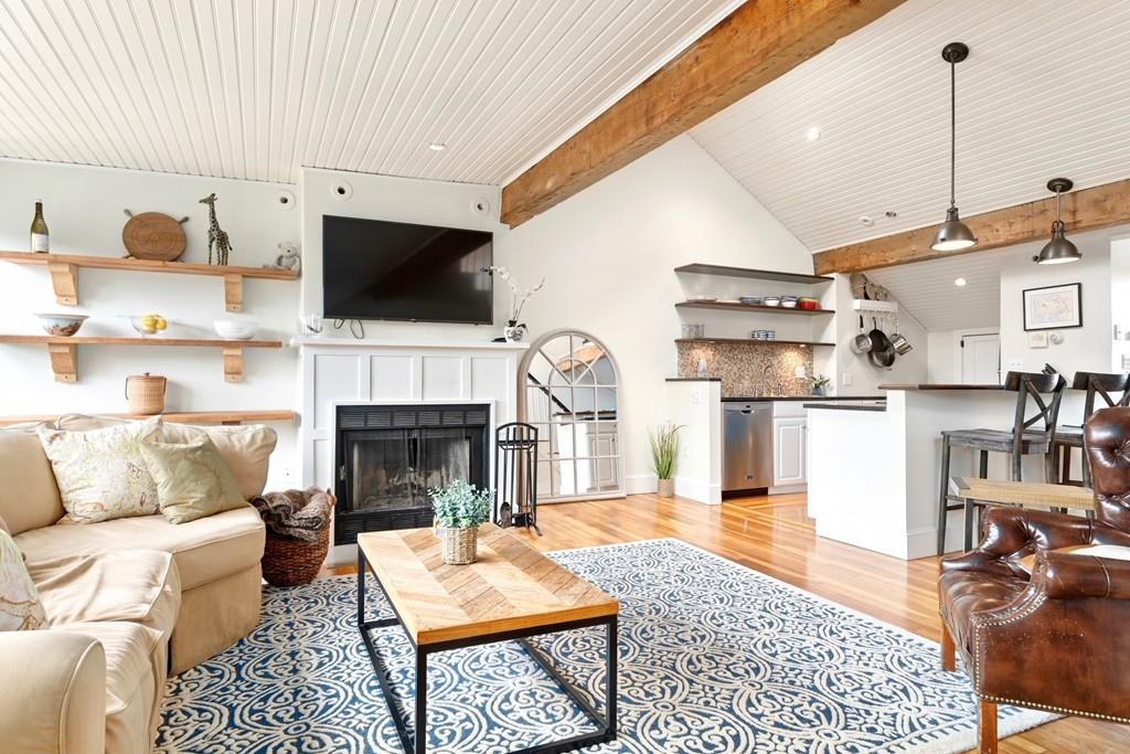 An open living room with furniture and a fireplace, and exposed beams on the vaulted ceiling.