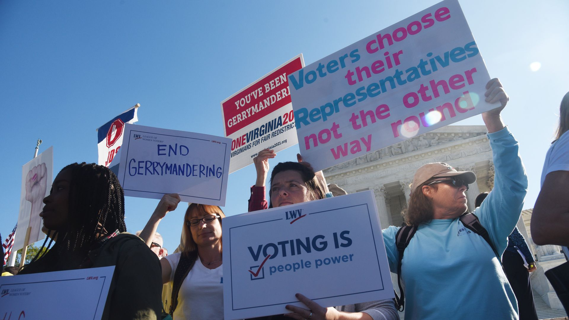 People hold signs about voting rights.
