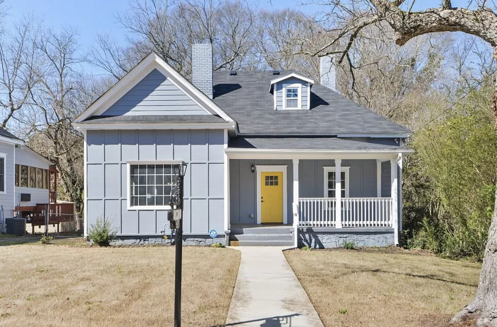 Slate gray house with yellow door and covered porch.