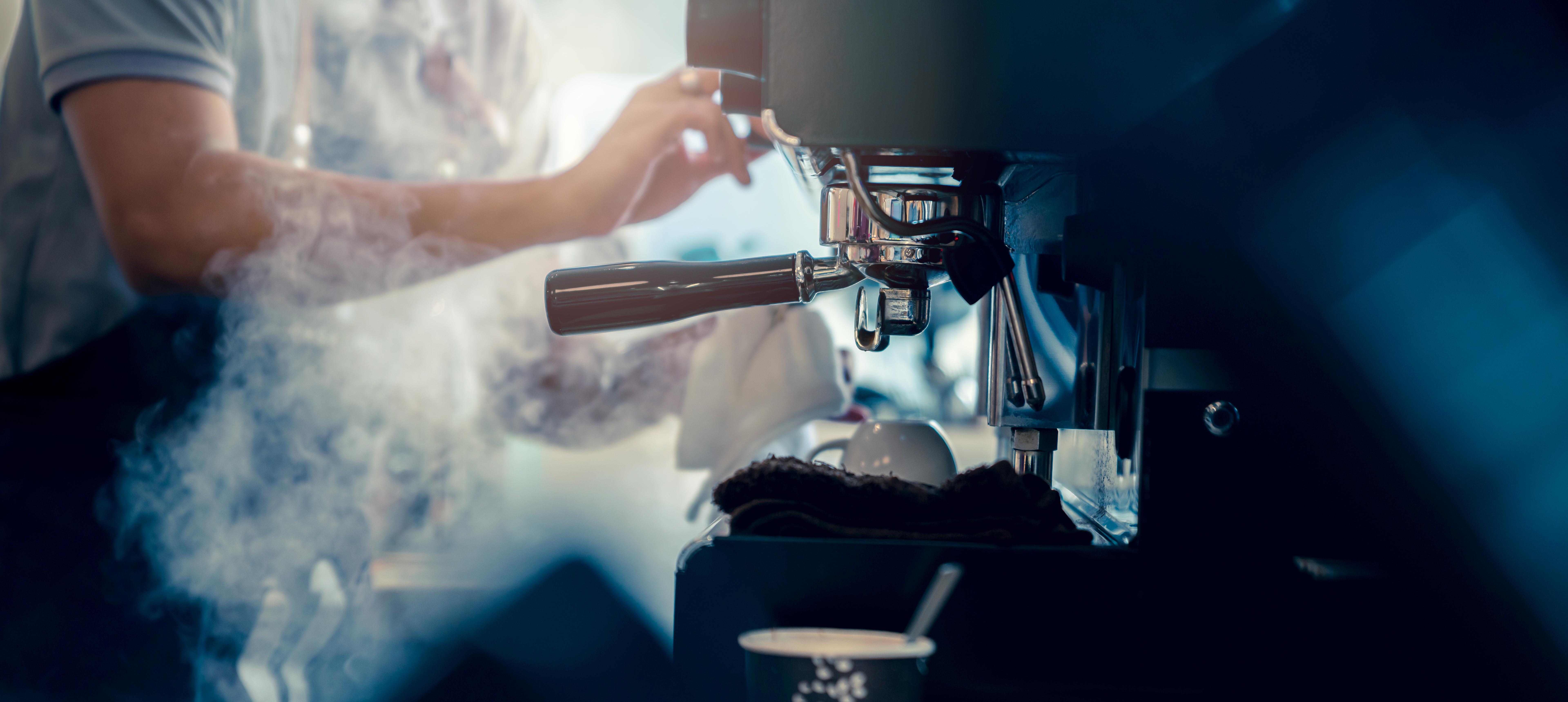 Hands working an espresso machine.
