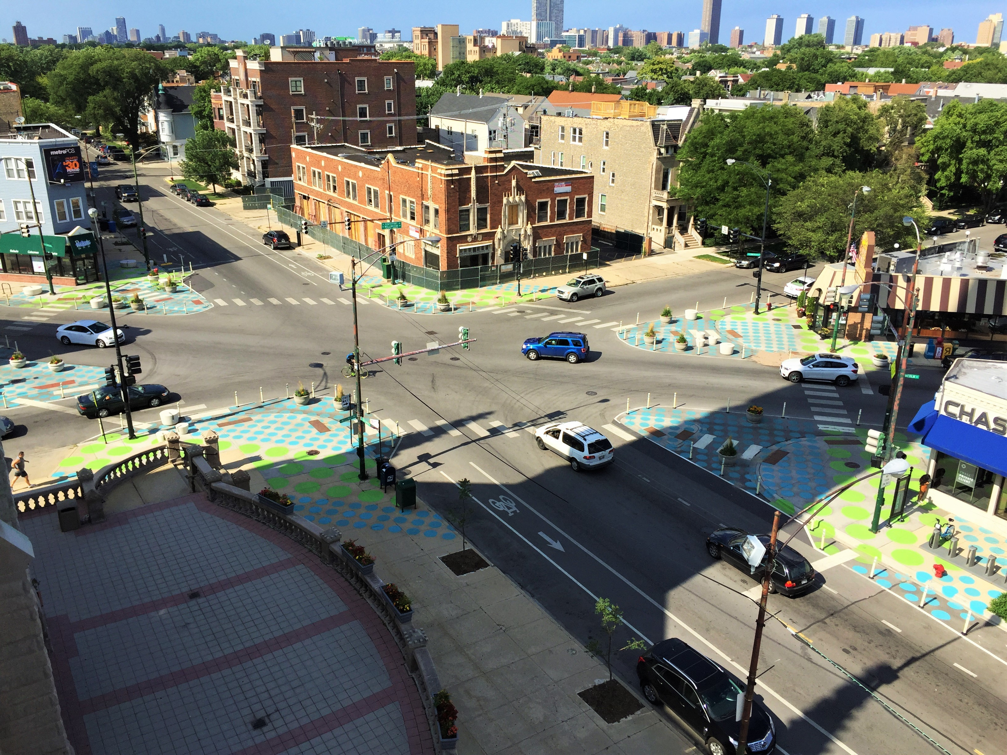 A busy intersection where several streets meet at different angles has been painted on each corner with polka-dots to create pedestrian plazas.