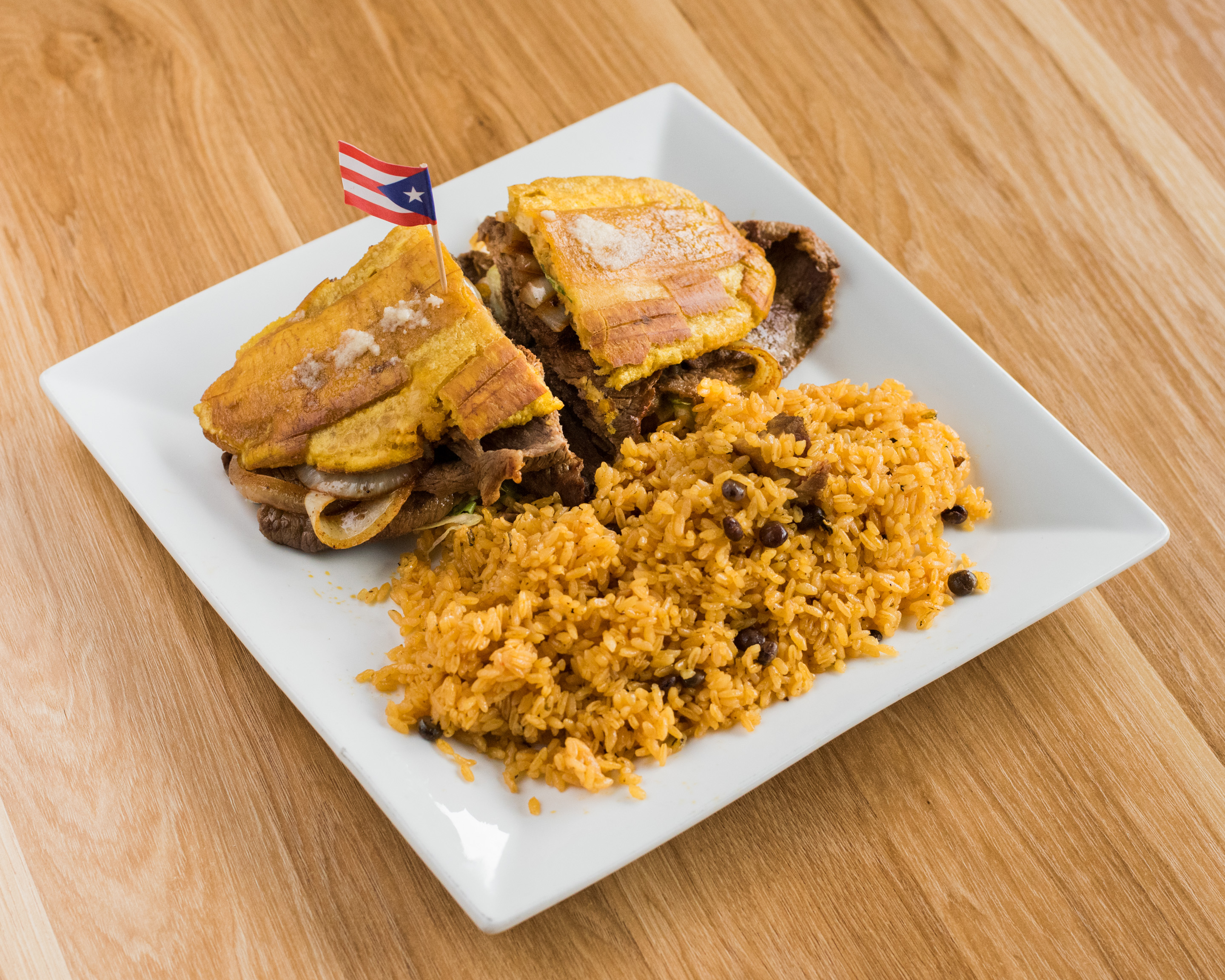 A jibarito sandwich with a side of rice.