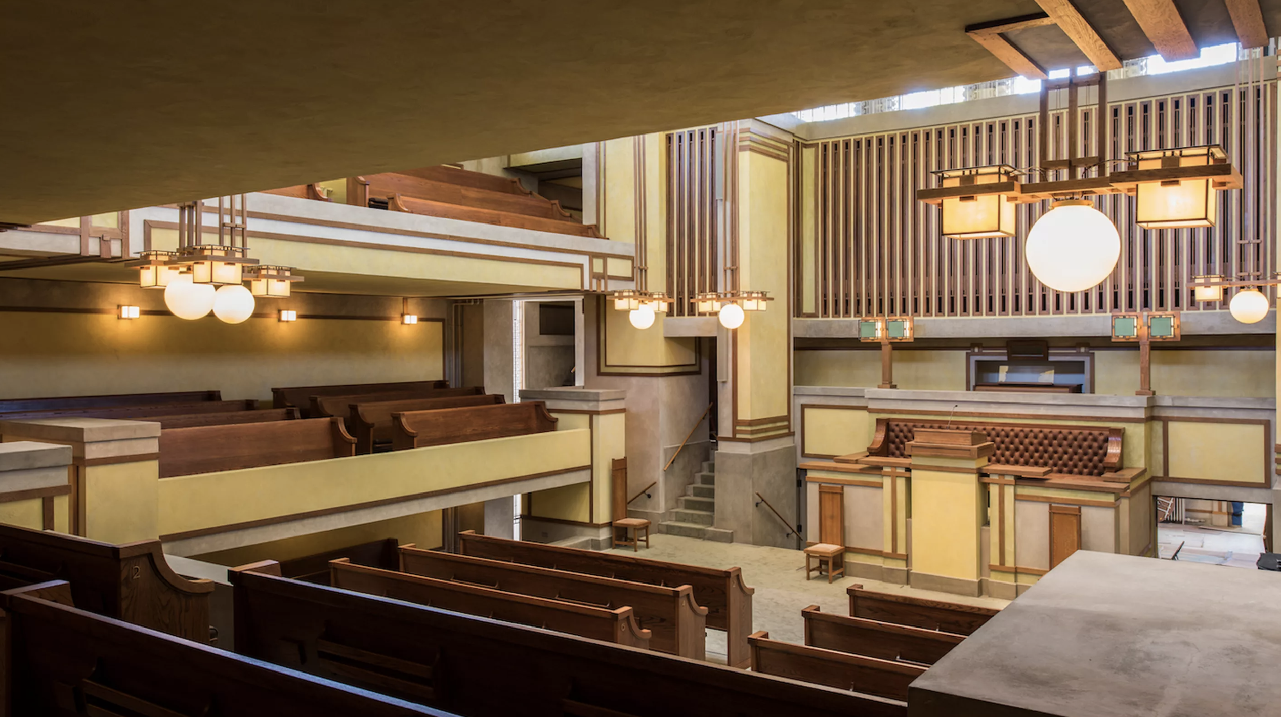 The sanctuary of a Frank Lloyd Wright-designed Unitarian Universalist church. The square room has wooden pews and three levels of seating. the walls are earth toned with wood trim and the coffered ceiling is skylit.