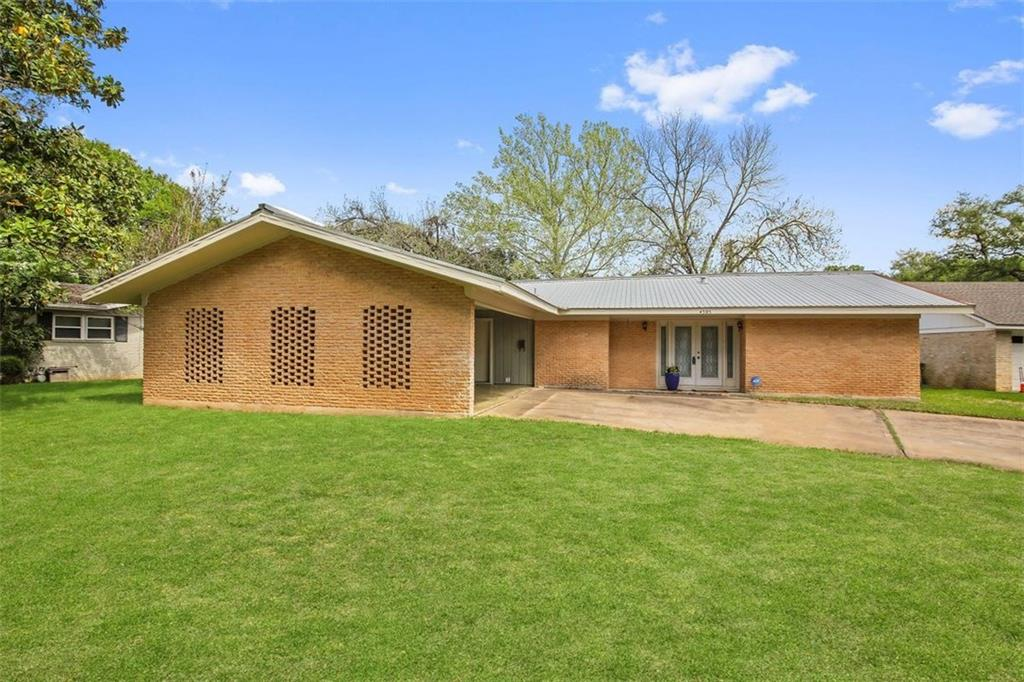 Exterior shot of a ranch-style home built in 1960. The garage extends out from the house and has a gabled roof. Its brick wall has three symmetrical rectangular shapes made of breeze block. The house is brick.