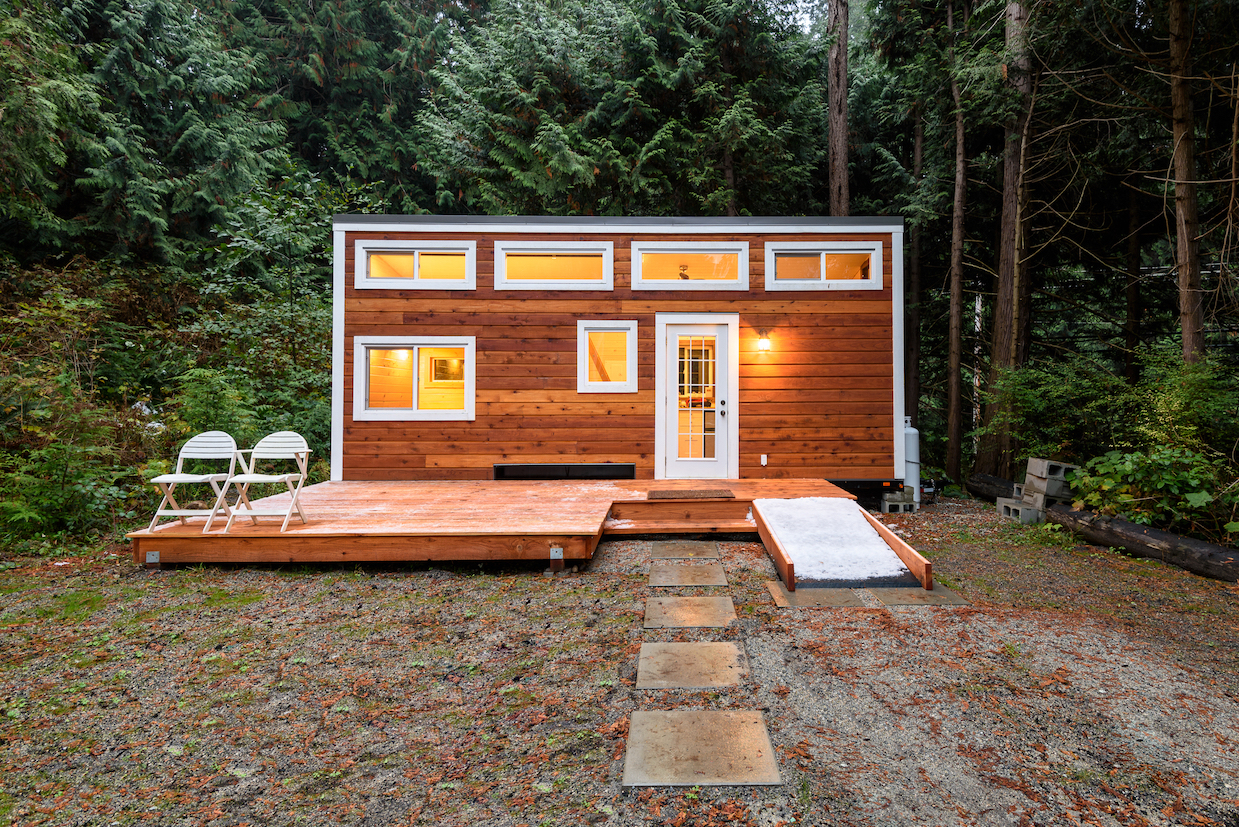 Tiny house with wood siding and small deck out front.