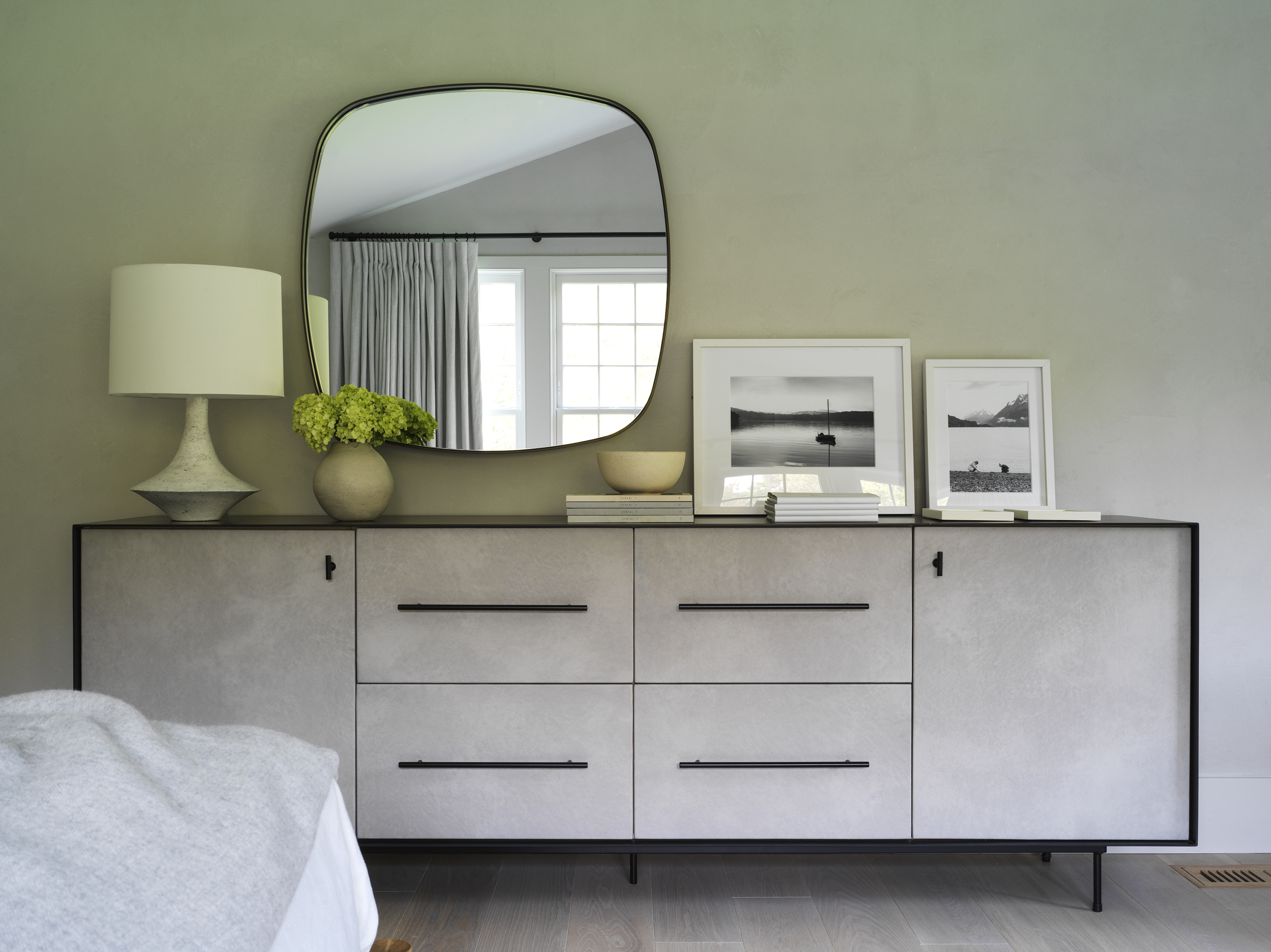 A beige dresser with a rounded square mirror hanging above.