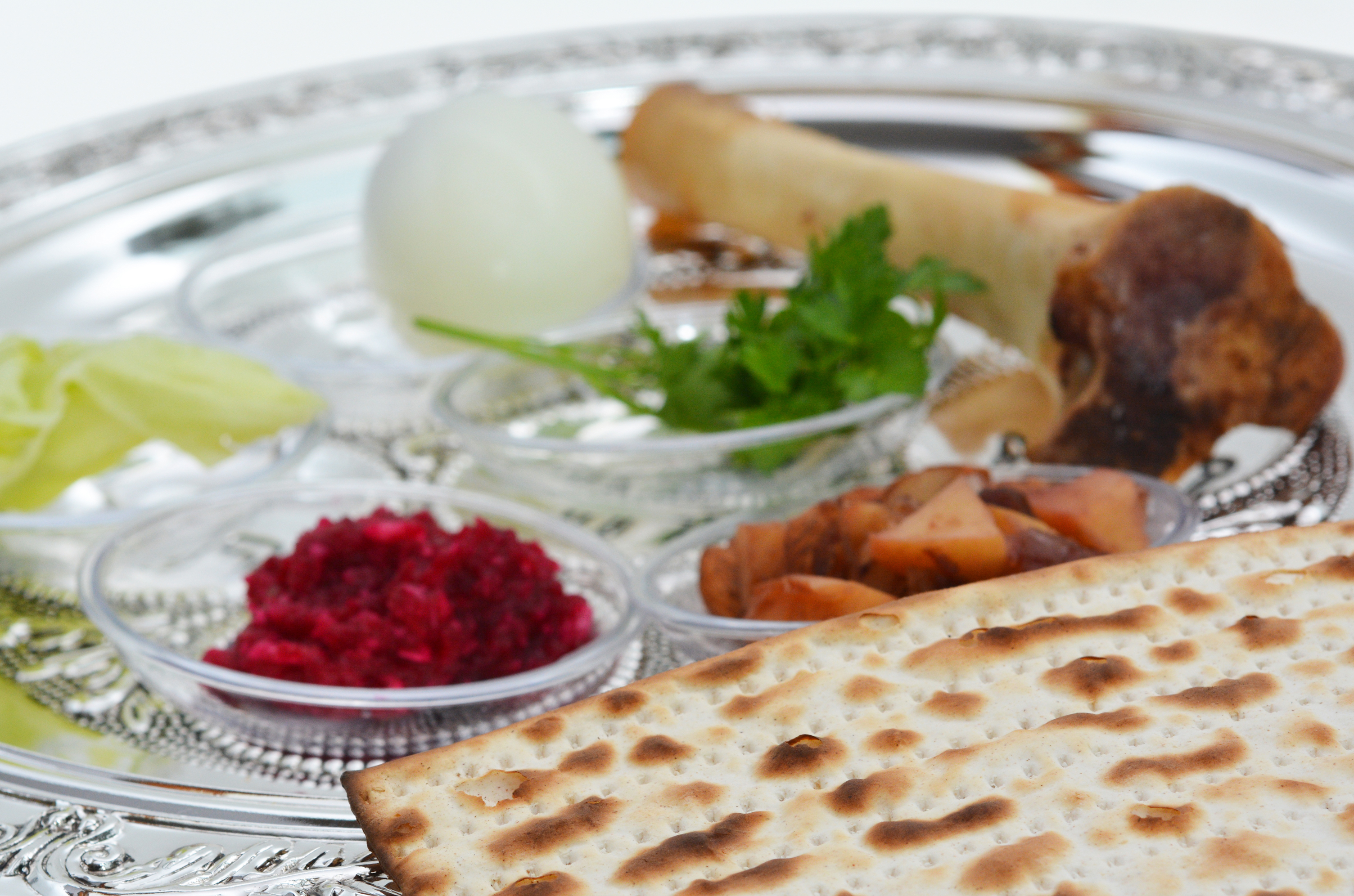 A closeup of a Seder plate with Matzah, lamb bone, and other items