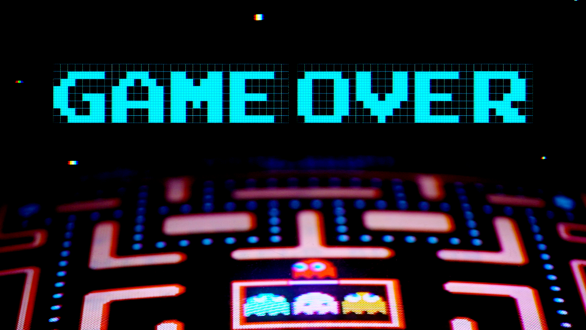 The word game over hovers above a Pac-Man arcade screen