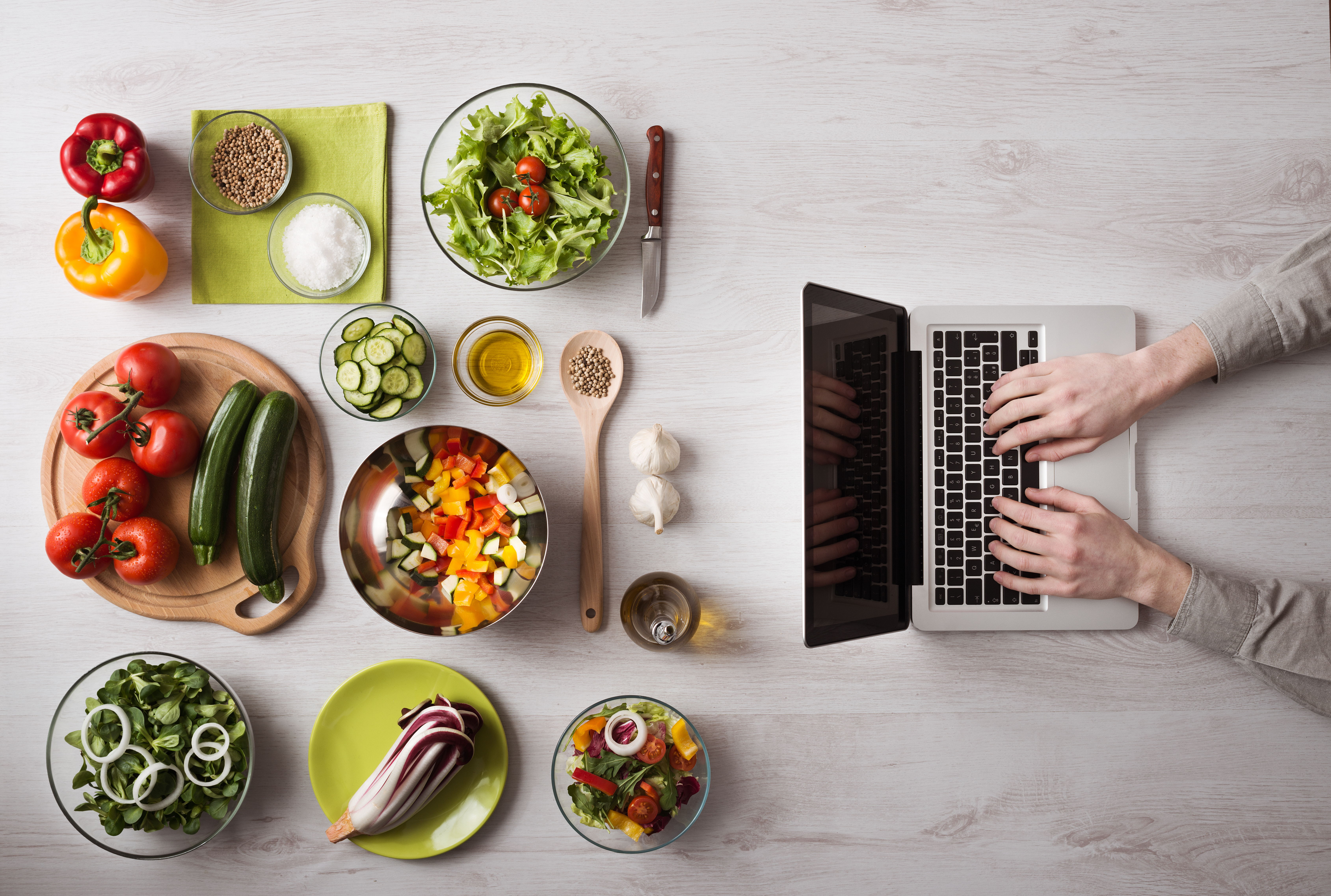 Someone types at a laptop in front of plates of food, mostly vegetables