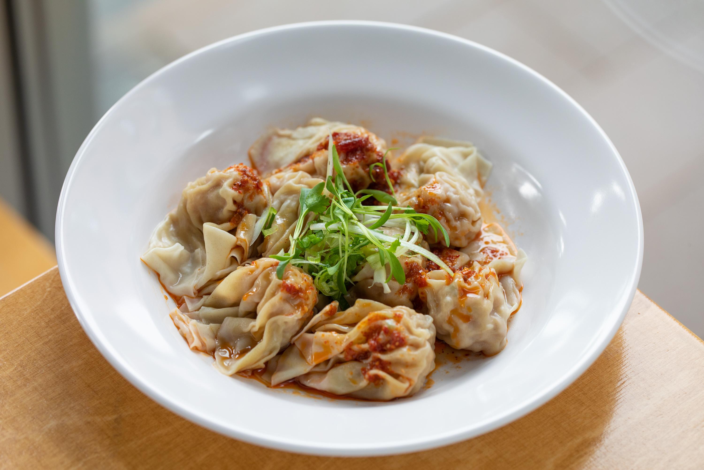 A plate of dumplings with sauce from a restaurant called Dumpling Monster.