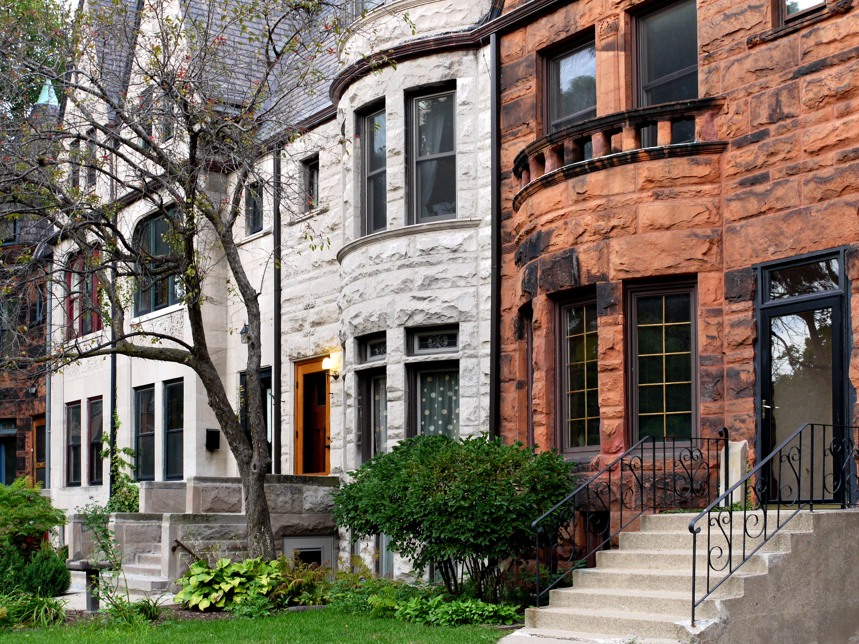 A row of gray and brown stone mansions on a residential street in Kenwood.