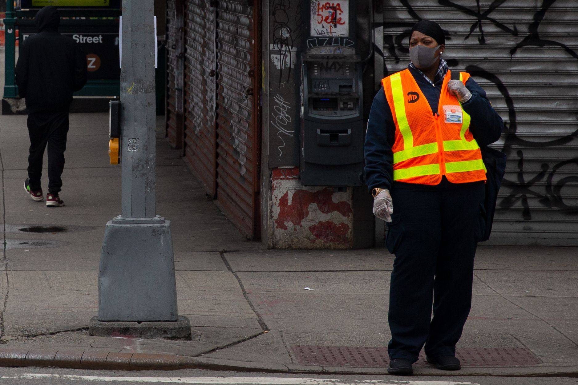 An MTA worker waits to cross Delancey Street during the coronavirus outbreak.