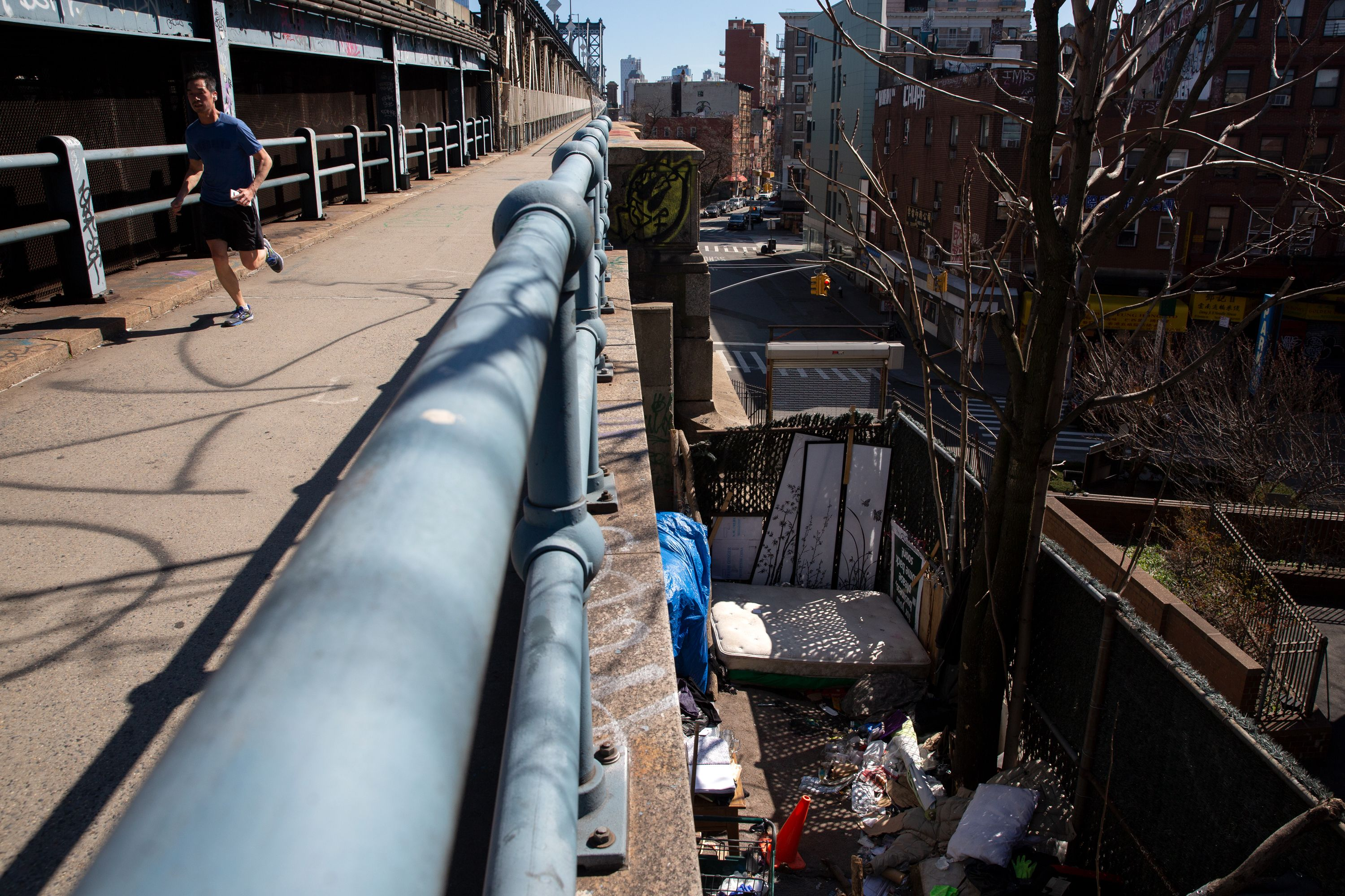 A homeless encampment on the side of the Manhattan Bridge in Chinatown.