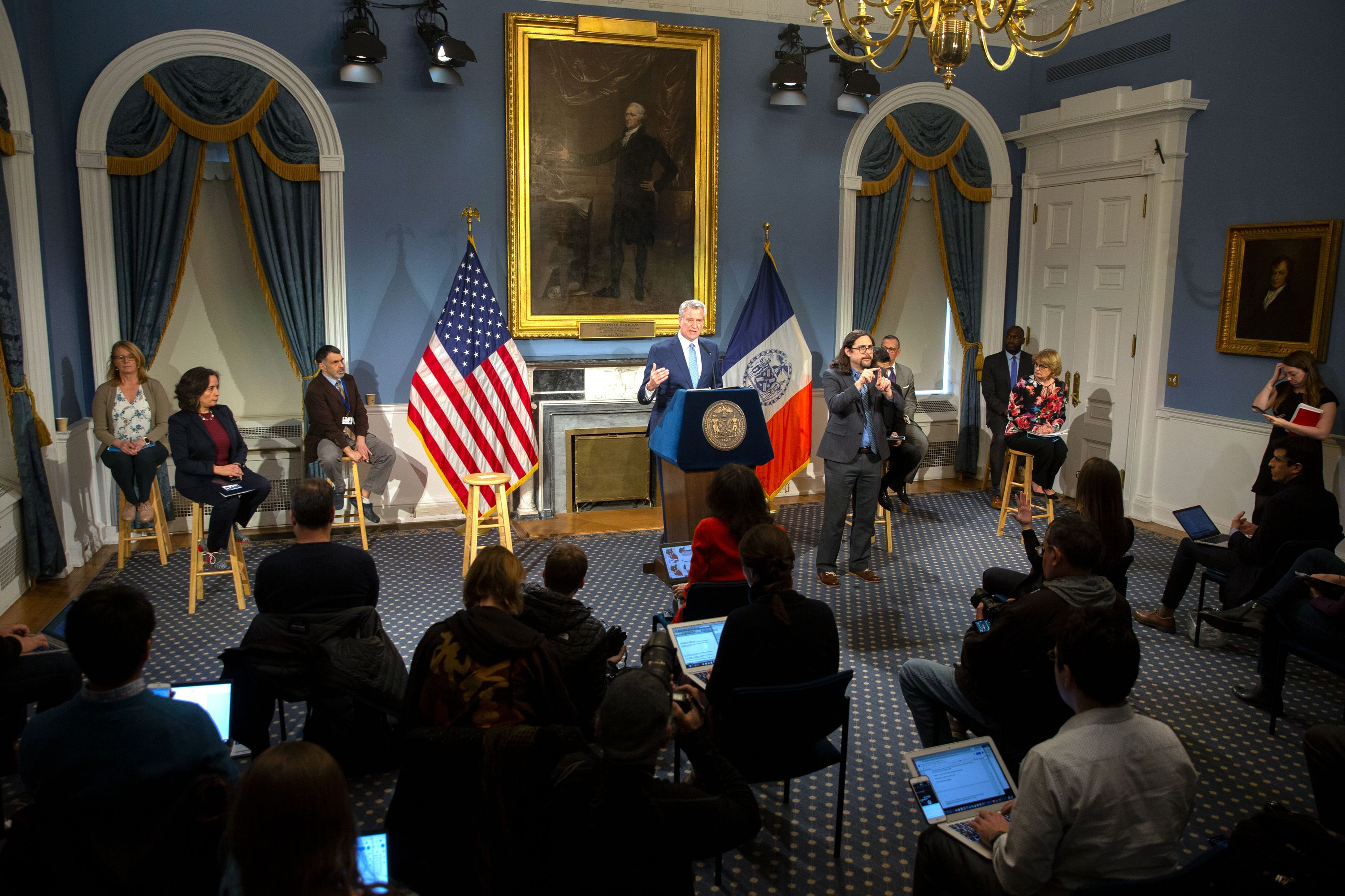 Government officials and journalists were separated during a City Hall press conference to help protect against the spread of the coronavirus.
