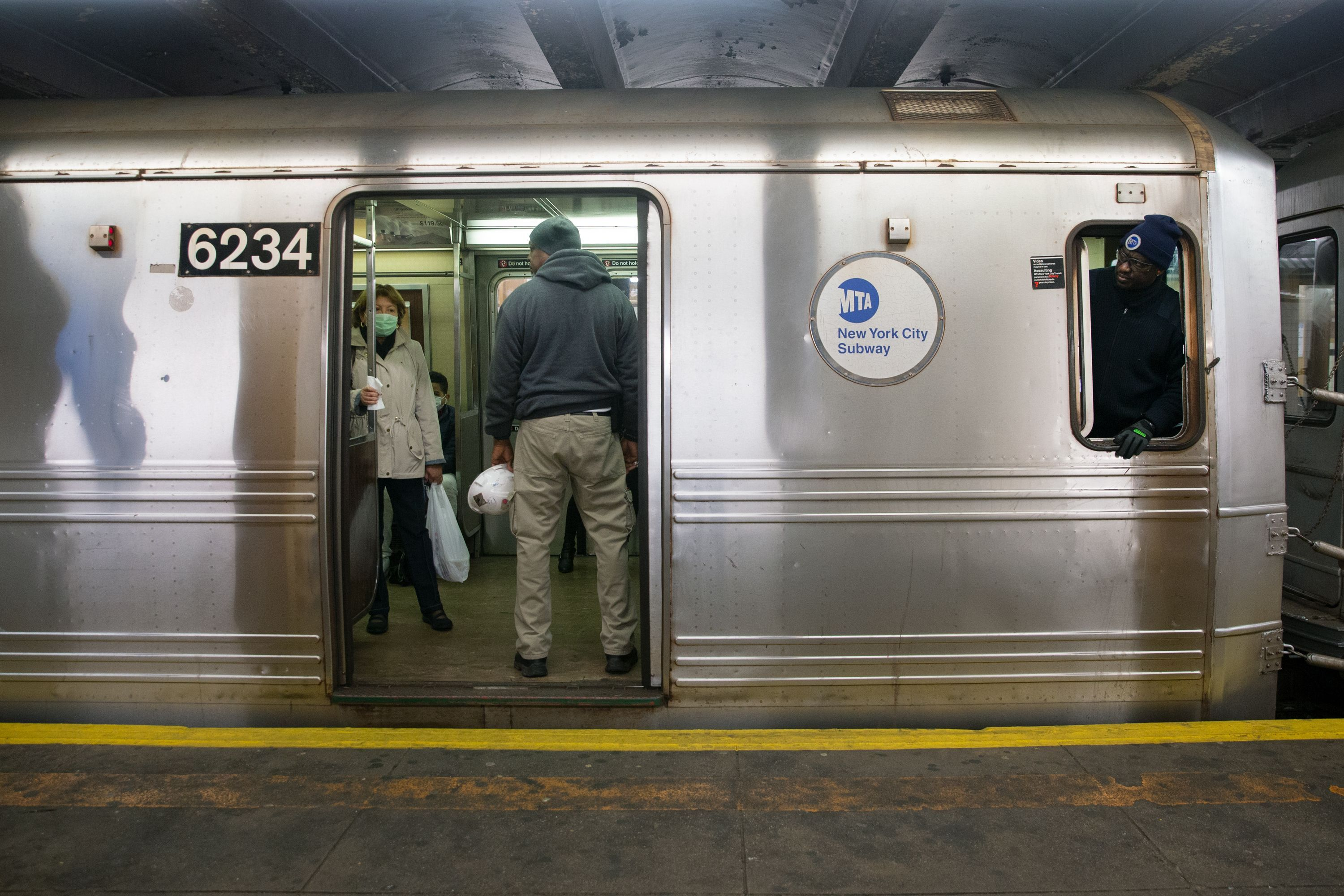 An MTA conductor checks the doors of an A train at the Nostrand Avenue station.
