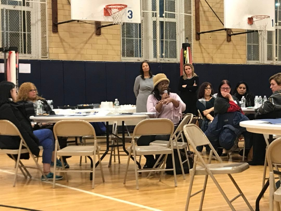 A parent speaks during a state-hosted meeting at Fort Hamilton High School to hear what families, teachers, and students think should be required to earn a diploma in New York.
