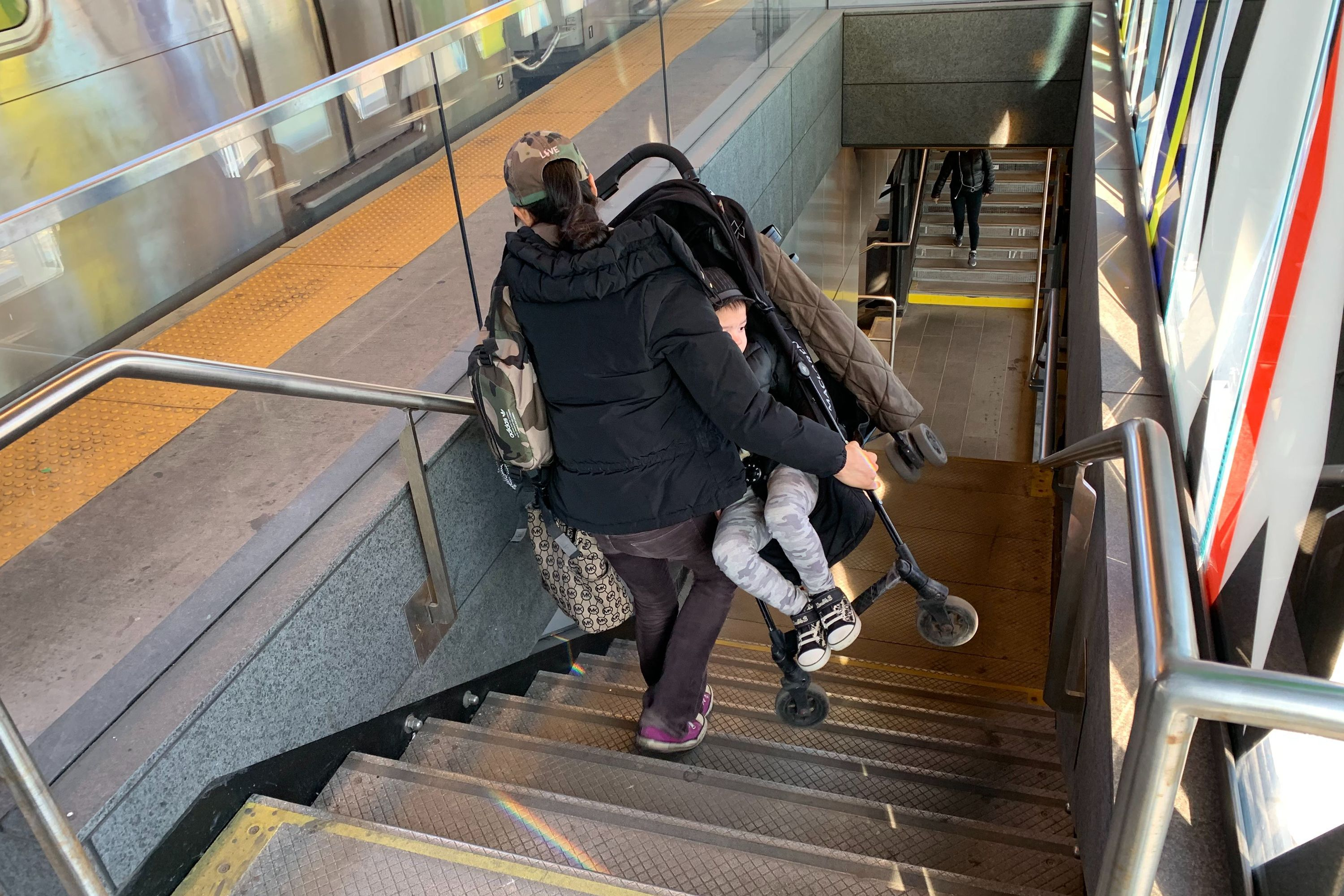 A woman carries a stroller down the steps at the 39 Avenue stop in Queens.