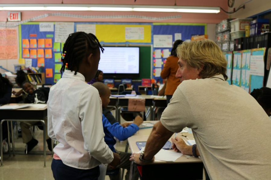A teacher at P.S. 398 in Crown Heights works with a student. With about half of their students experiencing homelessness, the school has a guidance counselor, a social worker, and a psychologist.