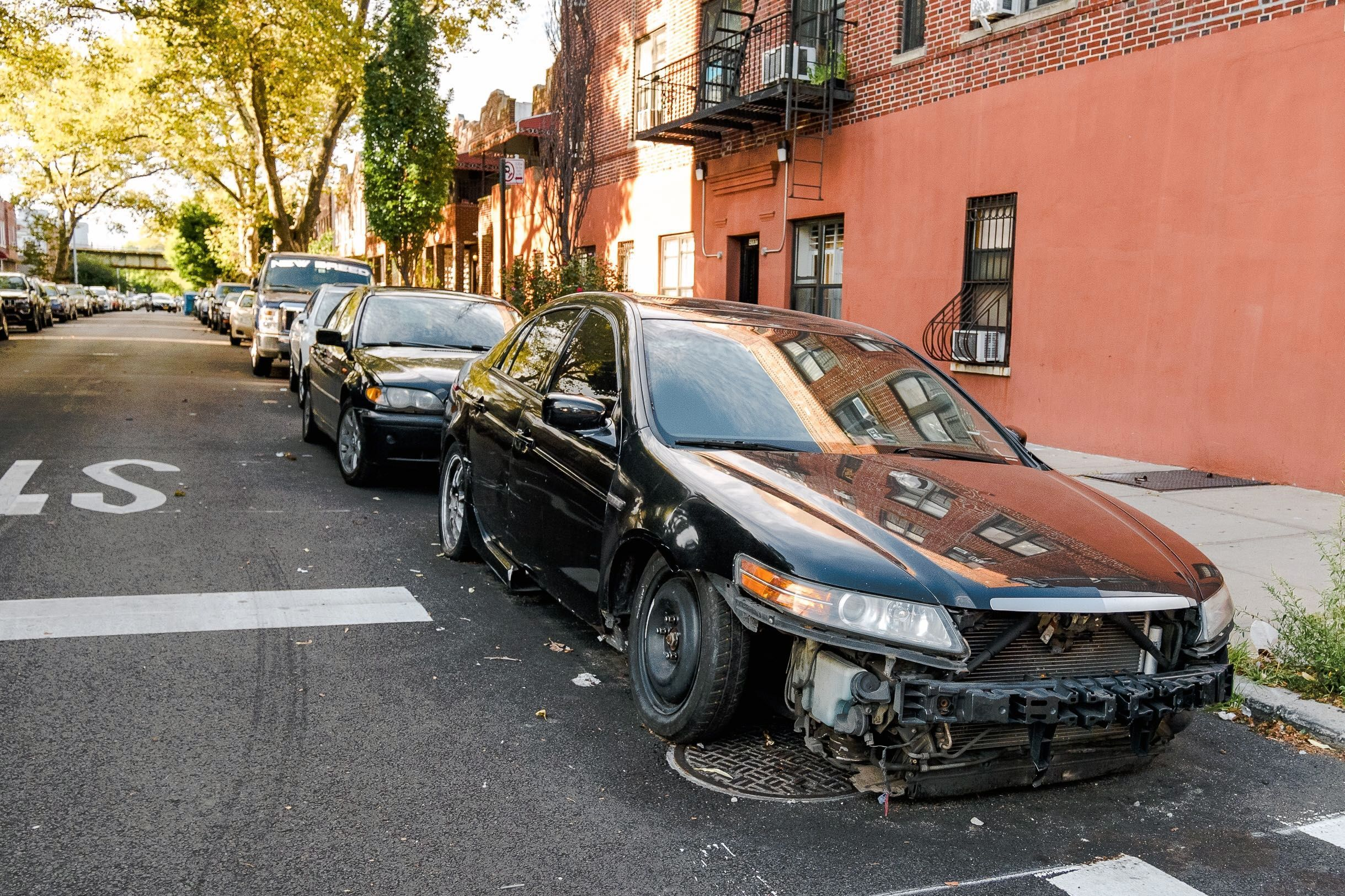 An abandoned car sits on a Brownsville, Brooklyn residential block, Sept. 1, 2019.