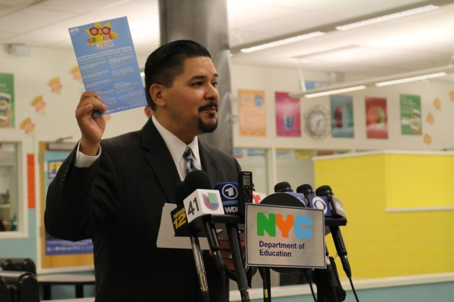 """Chancellor Richard Carranza holds up a """"summer meals"""" branded envelope at a launch event for the free summer meals program."""