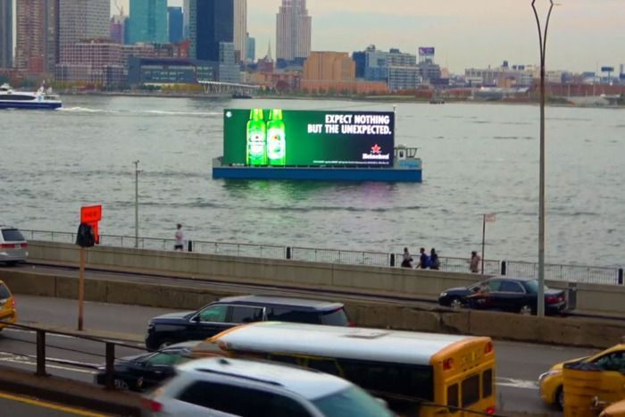 An advertising barge sails past motorists in Manhattan.