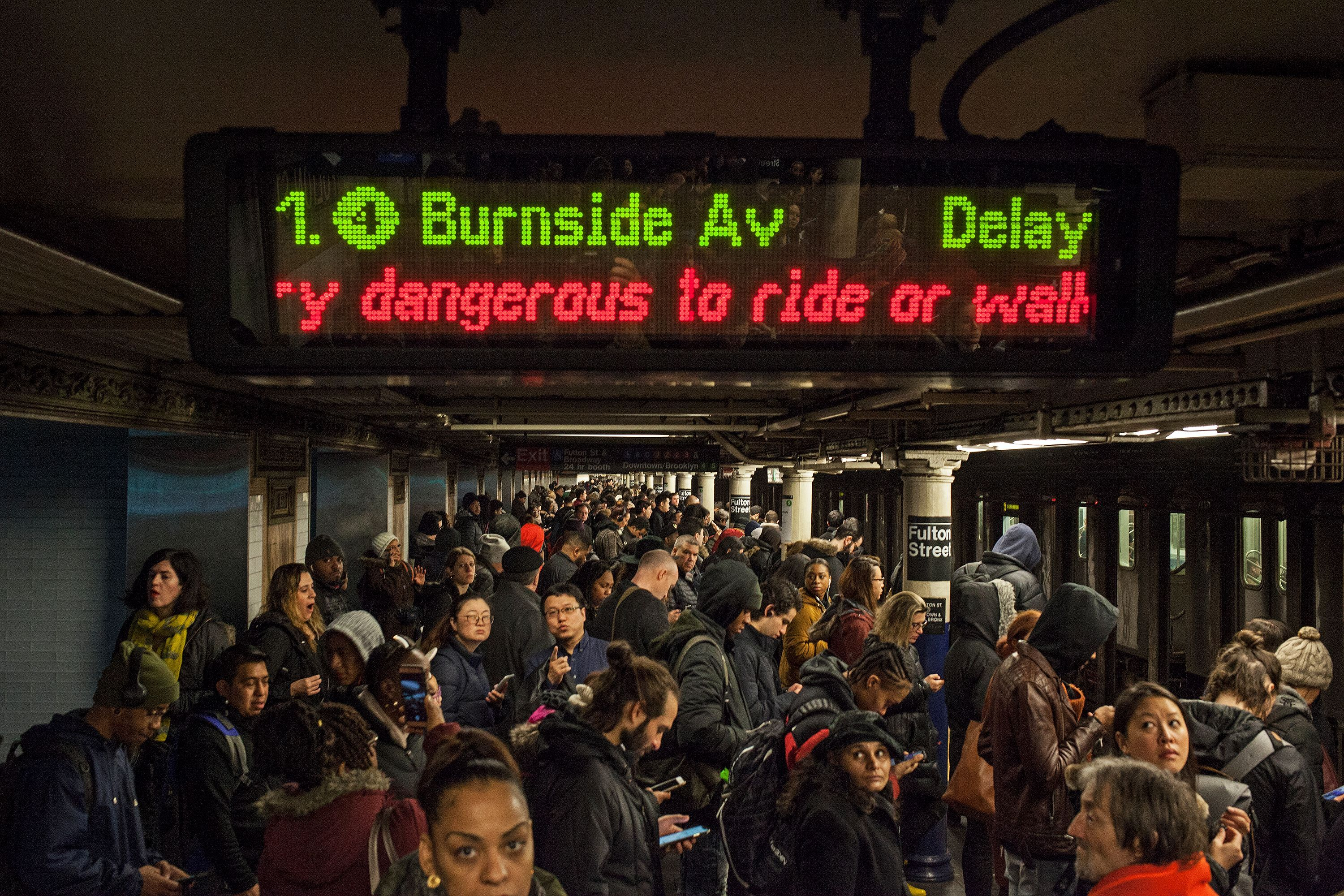 Riders wait for a 4 or 5 train at the Fulton Transit Center during a morning commute riddled with delays, Feb. 8, 2019.