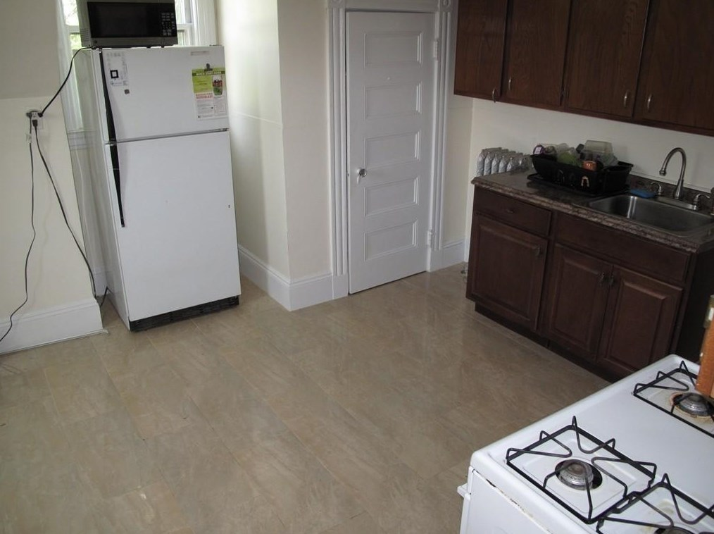 A kitchen with two separate counters across from a fridge.