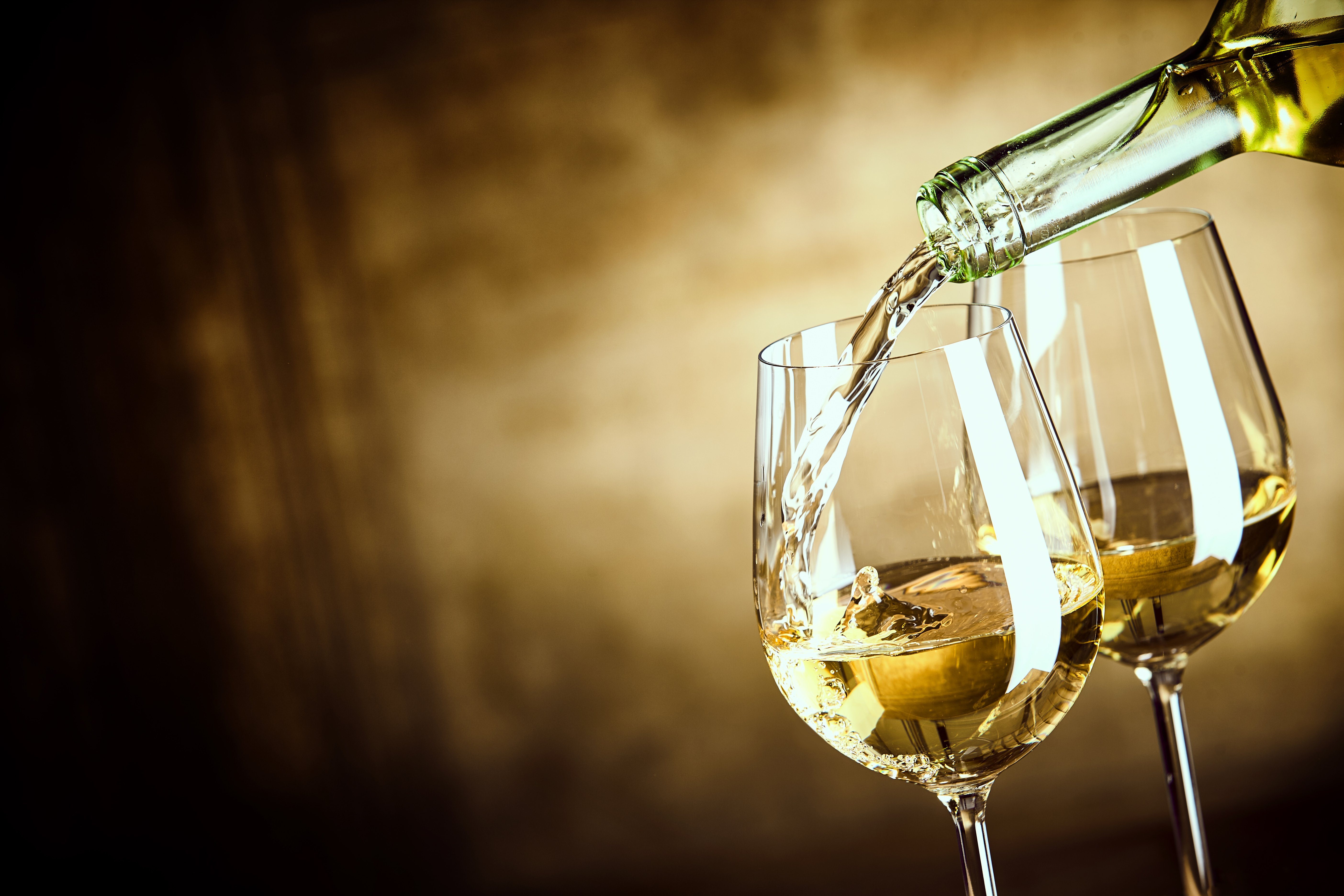 Two glasses of wine with white wine being poured into one of them