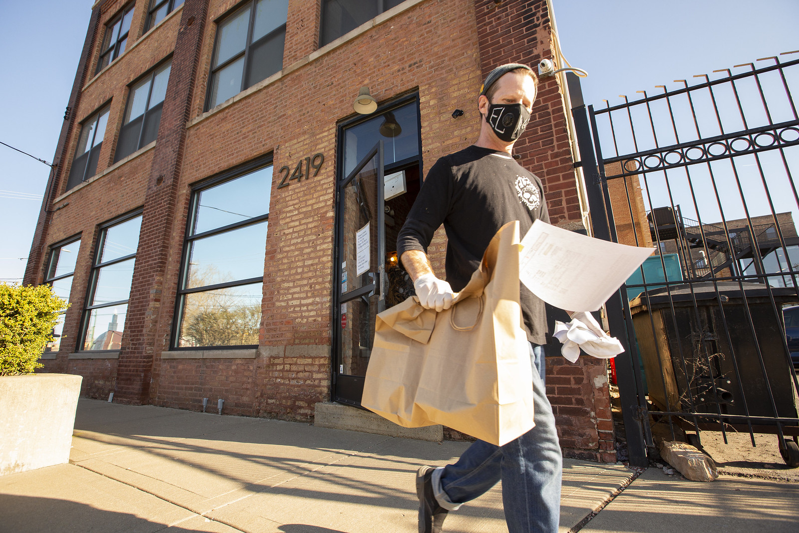 A man holding multiple brown paper bags outside.