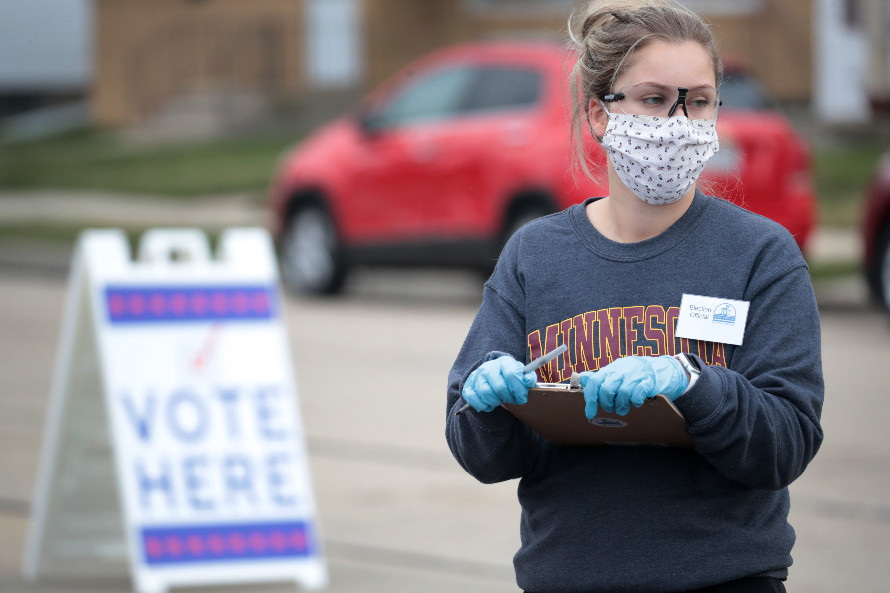 "A woman holding a clipboard and wearing a mask next to a ""vote here"" sign."