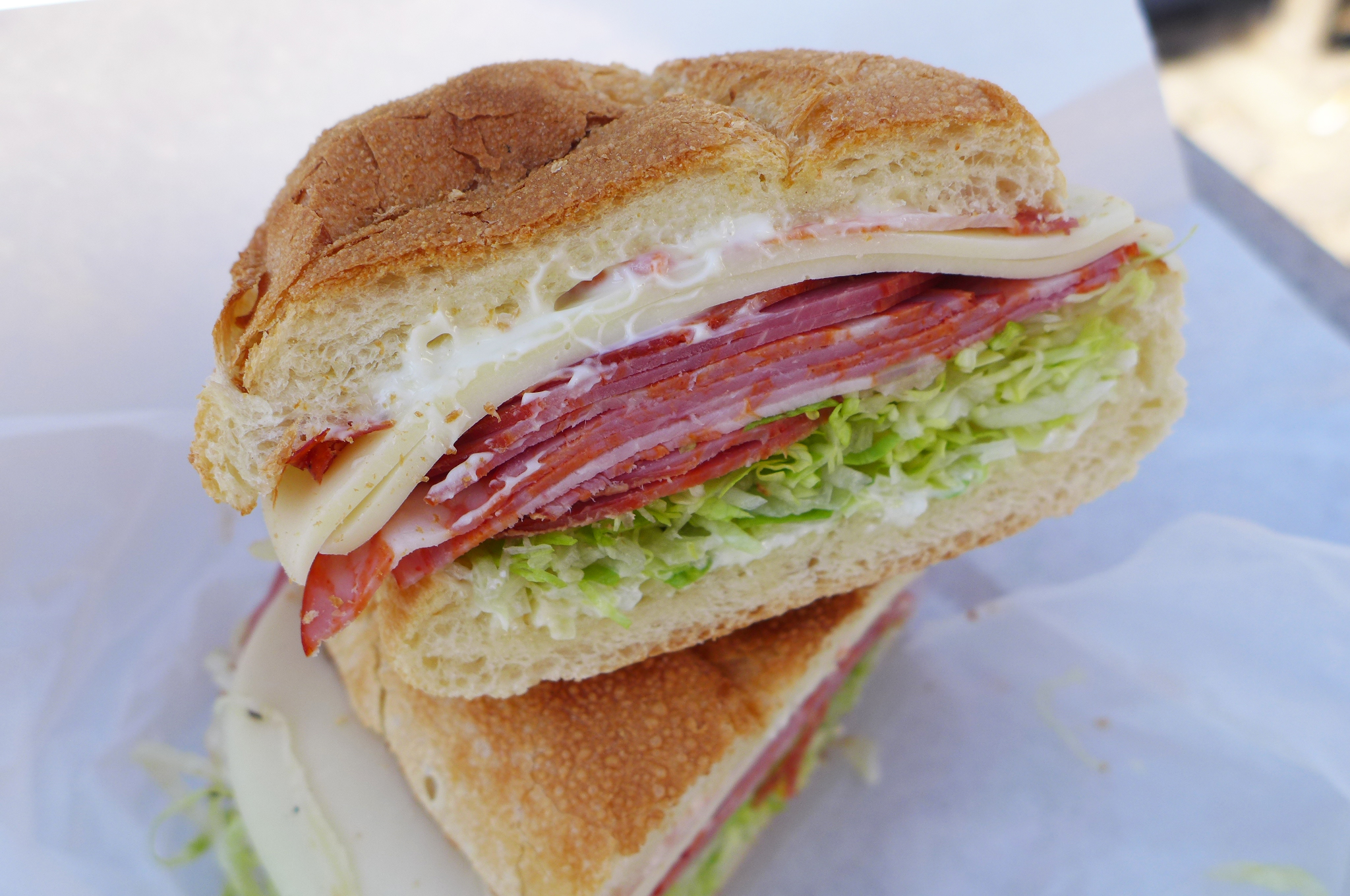 The sandwich shown in cross section with sausage, cheese, lettuce, tomato, and mayo.