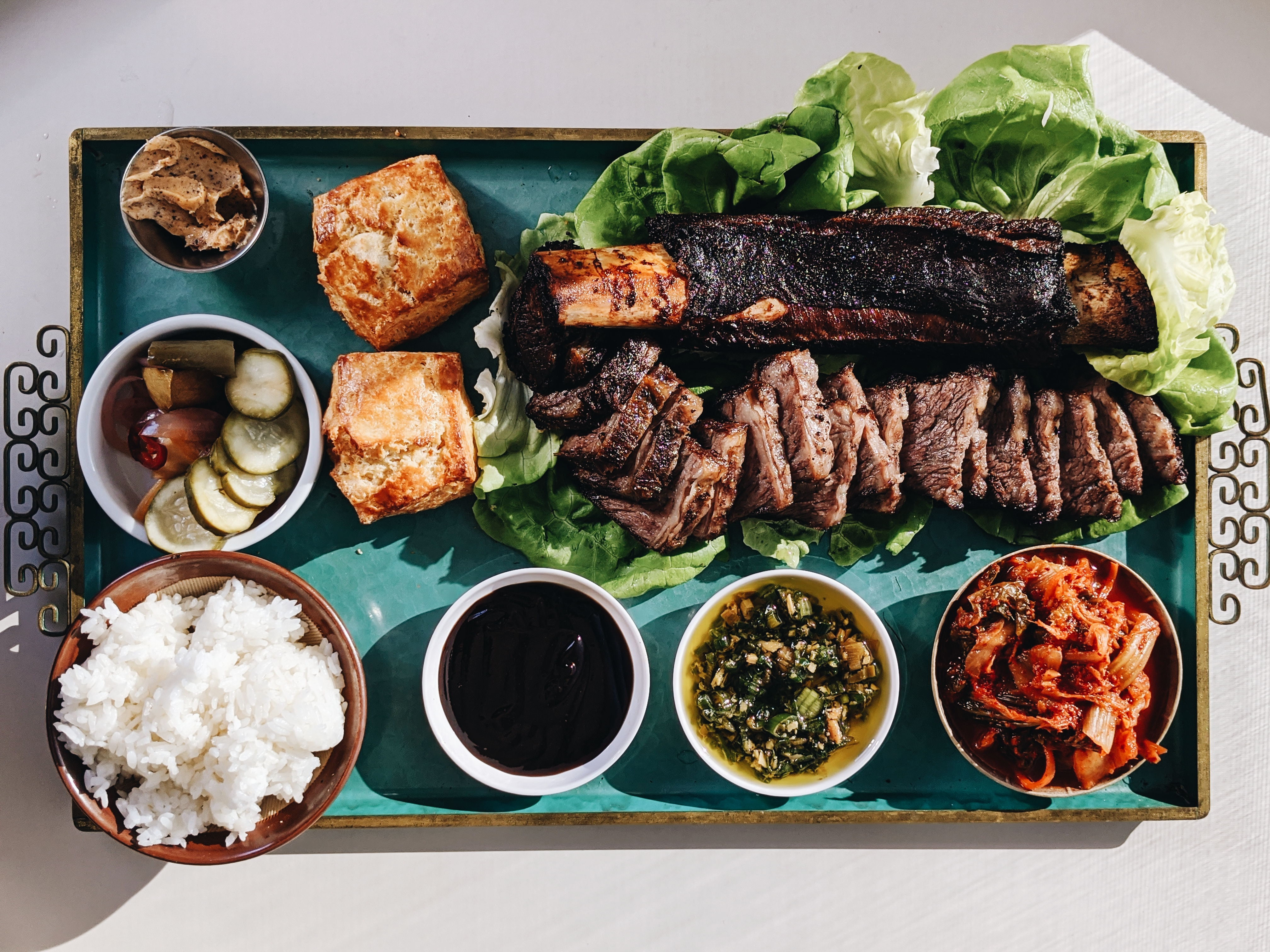 A tray of beef short ribs with kimchi, pickles, bibb lettuce, hoisin sauce, rice, ginger-scallion sauce at Bar King