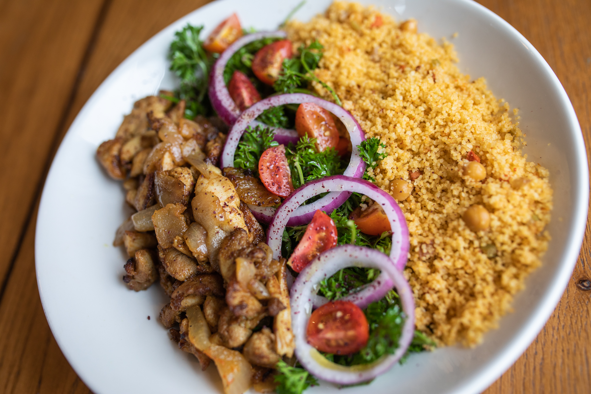 Pieces of cooked chicken with tomato, greens, sliced red onions, and a chickpea and rice blend on a white plate, which is sitting on a wooden table