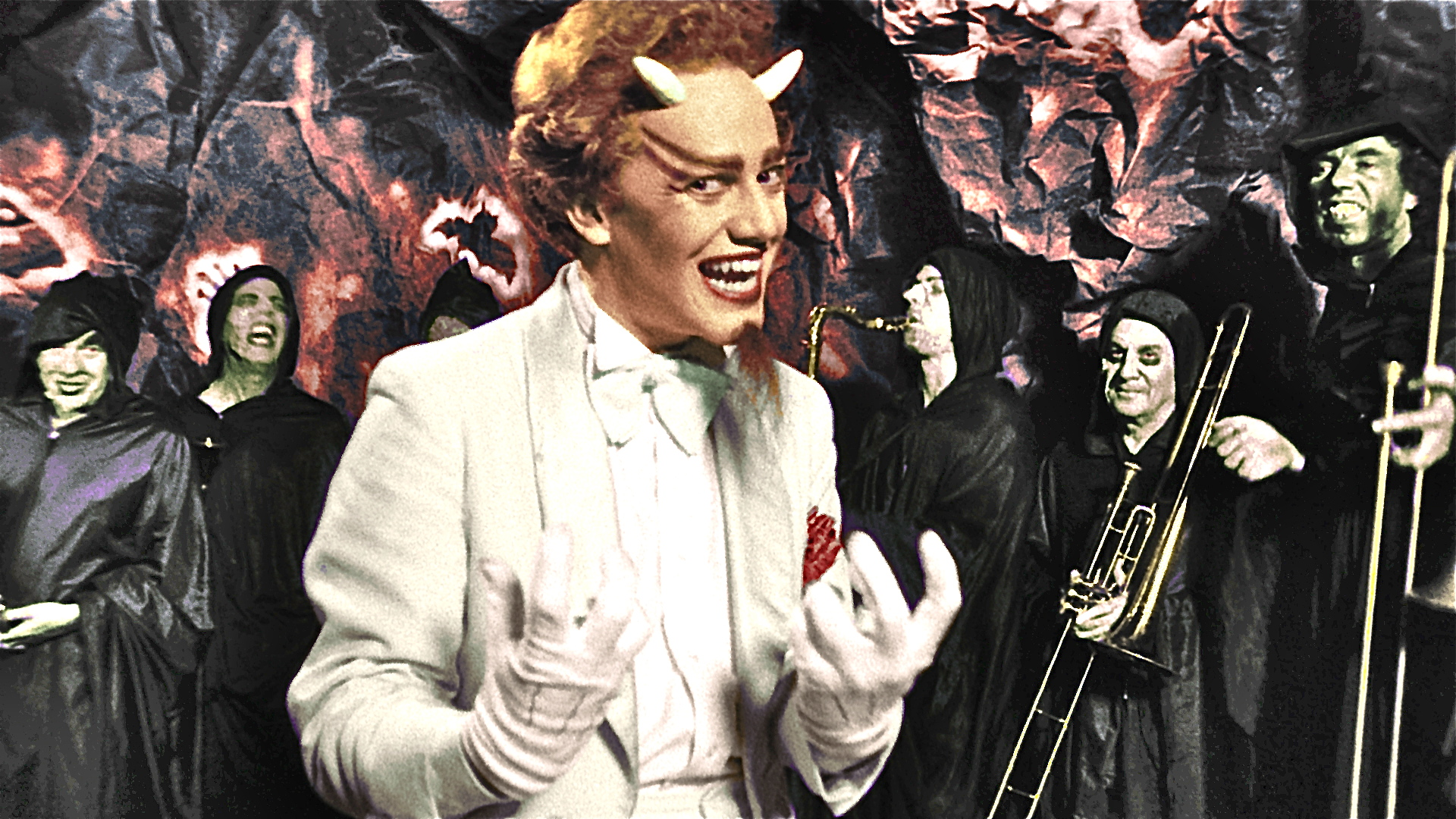 Composer Danny Elfman, as a grinning devil in his brother's movie Forbidden Zone, wears a white suit and a red wig, and stands in front of a band of horn-clasping musicians in green-skin makeup and black cultist robes.