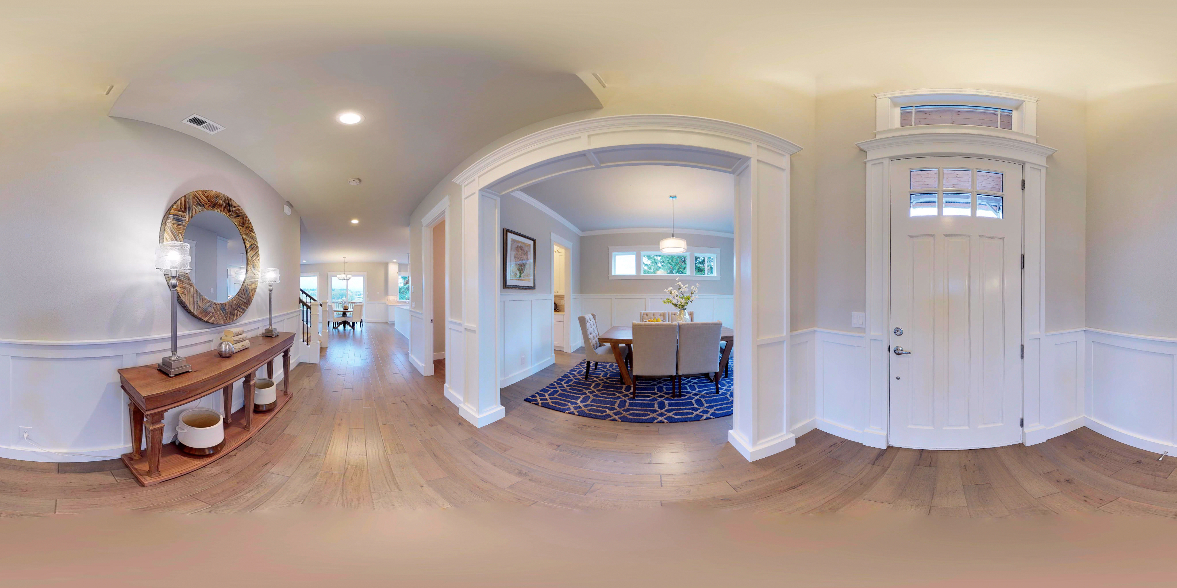 A stretched panoramic view of the foyer of a house.