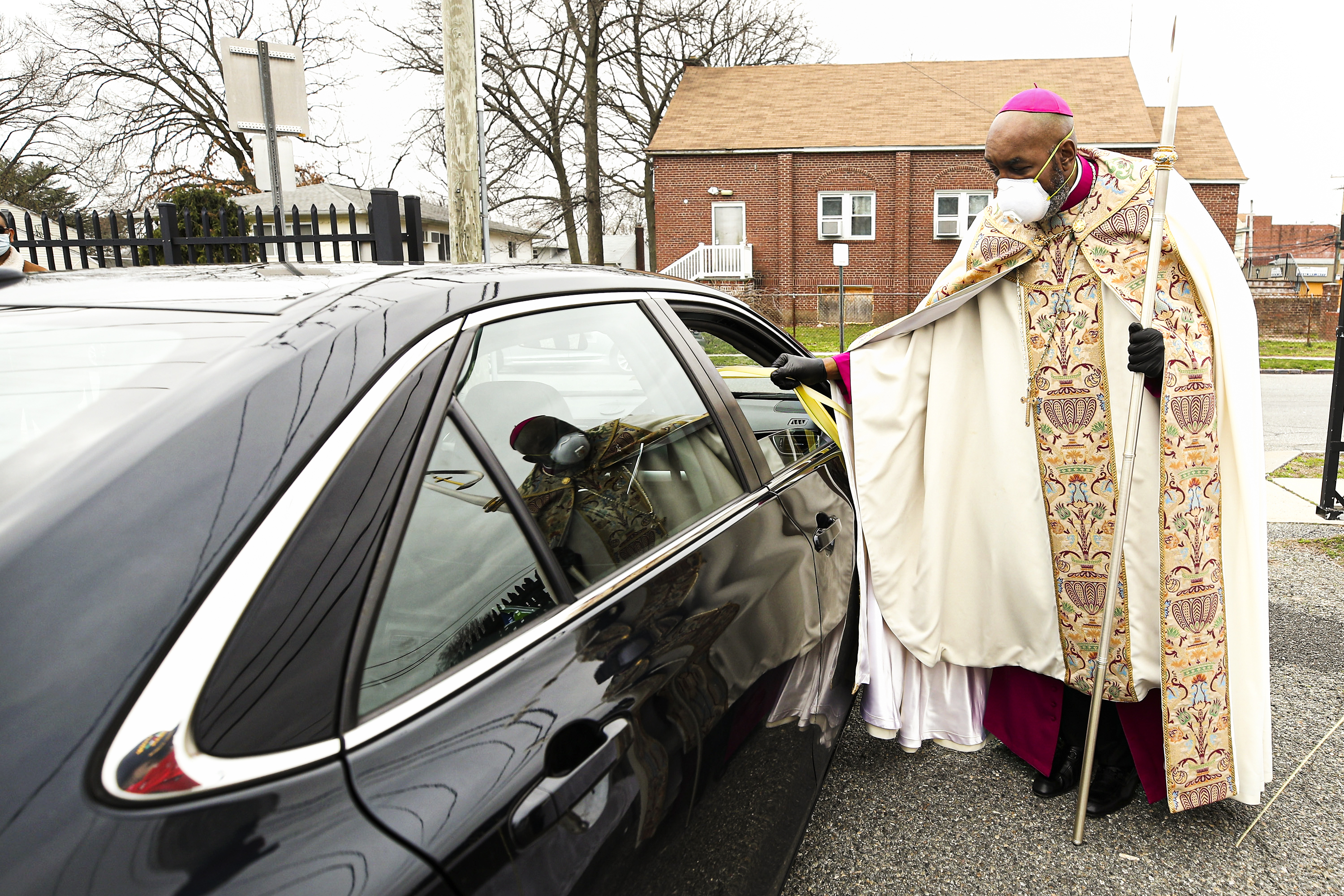 A person wearing clerical garb and a breathing mask stands in the parking lot of a church beside a car while reaching out to the person inside it.