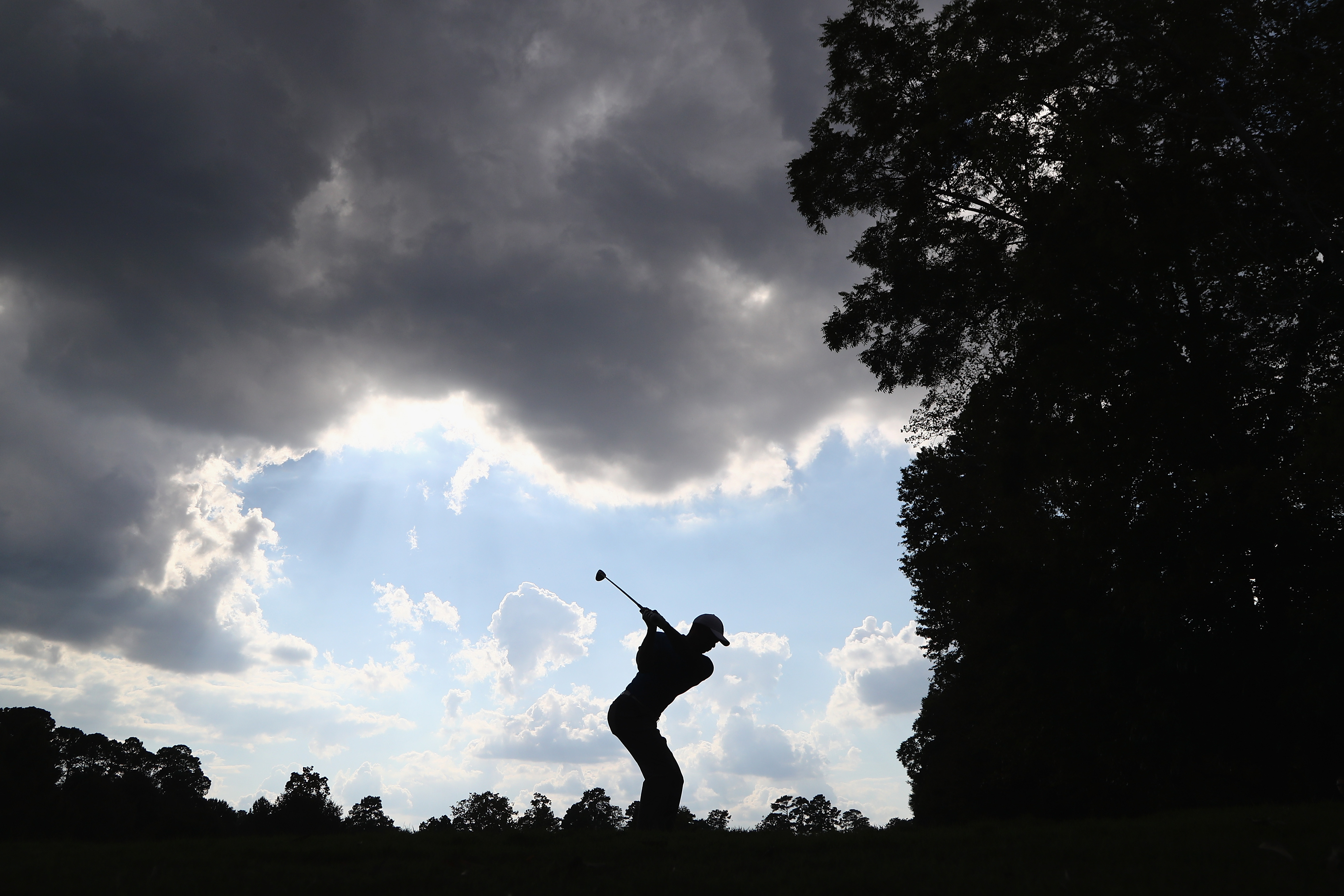 A photo of golf superstar Tiger Woods teeing off beneath an ominous dark cloud.