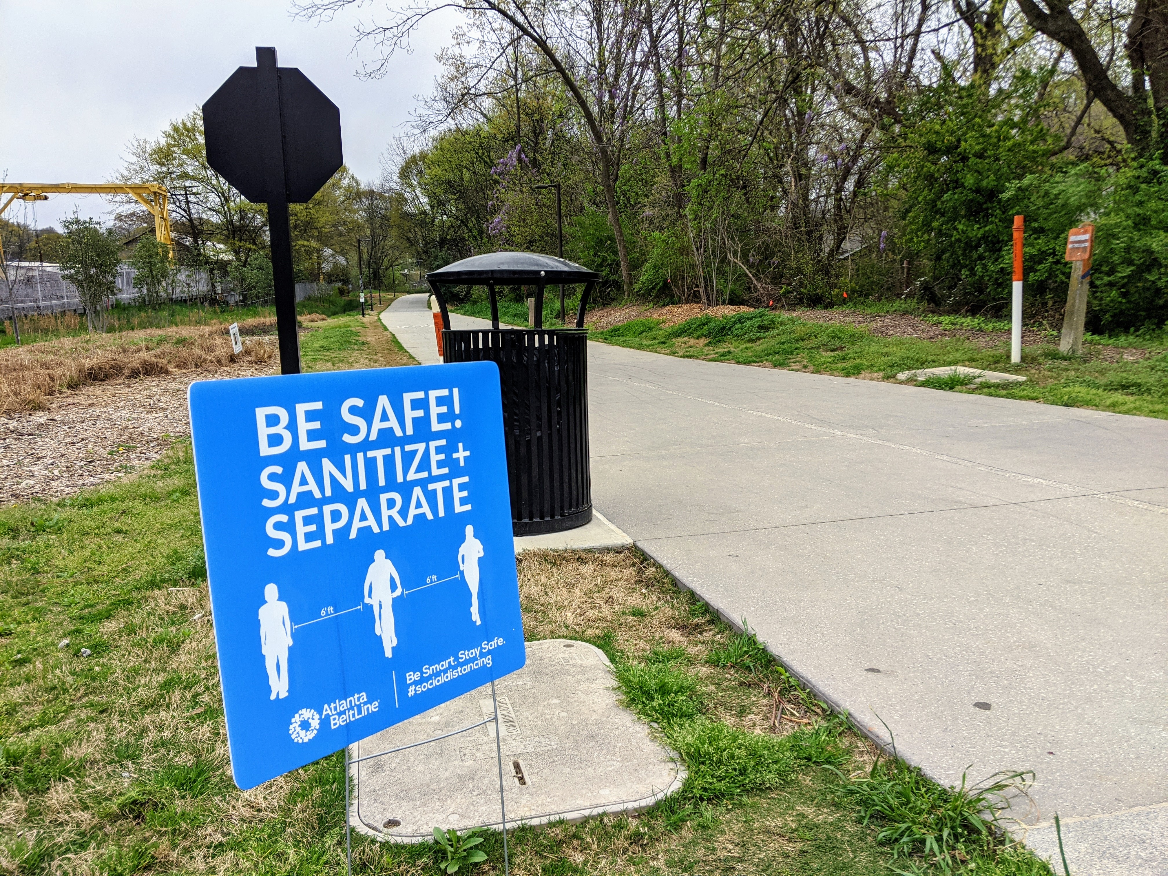 A photo of the Atlanta Beltline with a sign beside it urging people to keep apart from each other.