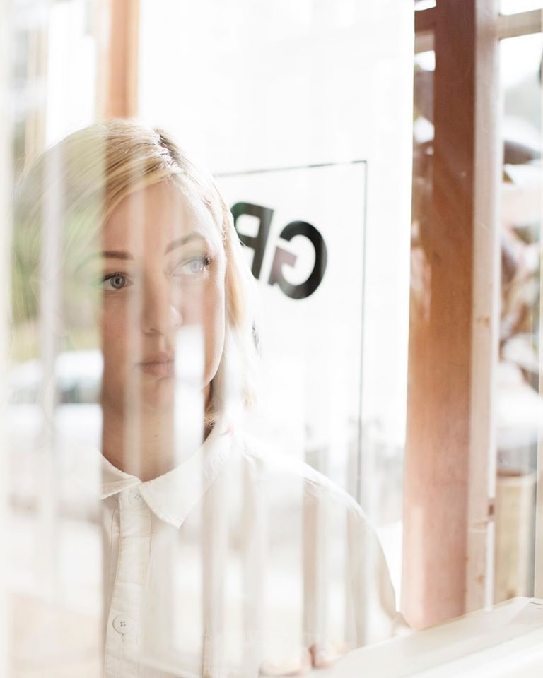 Jamie Malone gazes out a white gauze curtain just inside the door of Grand Cafe