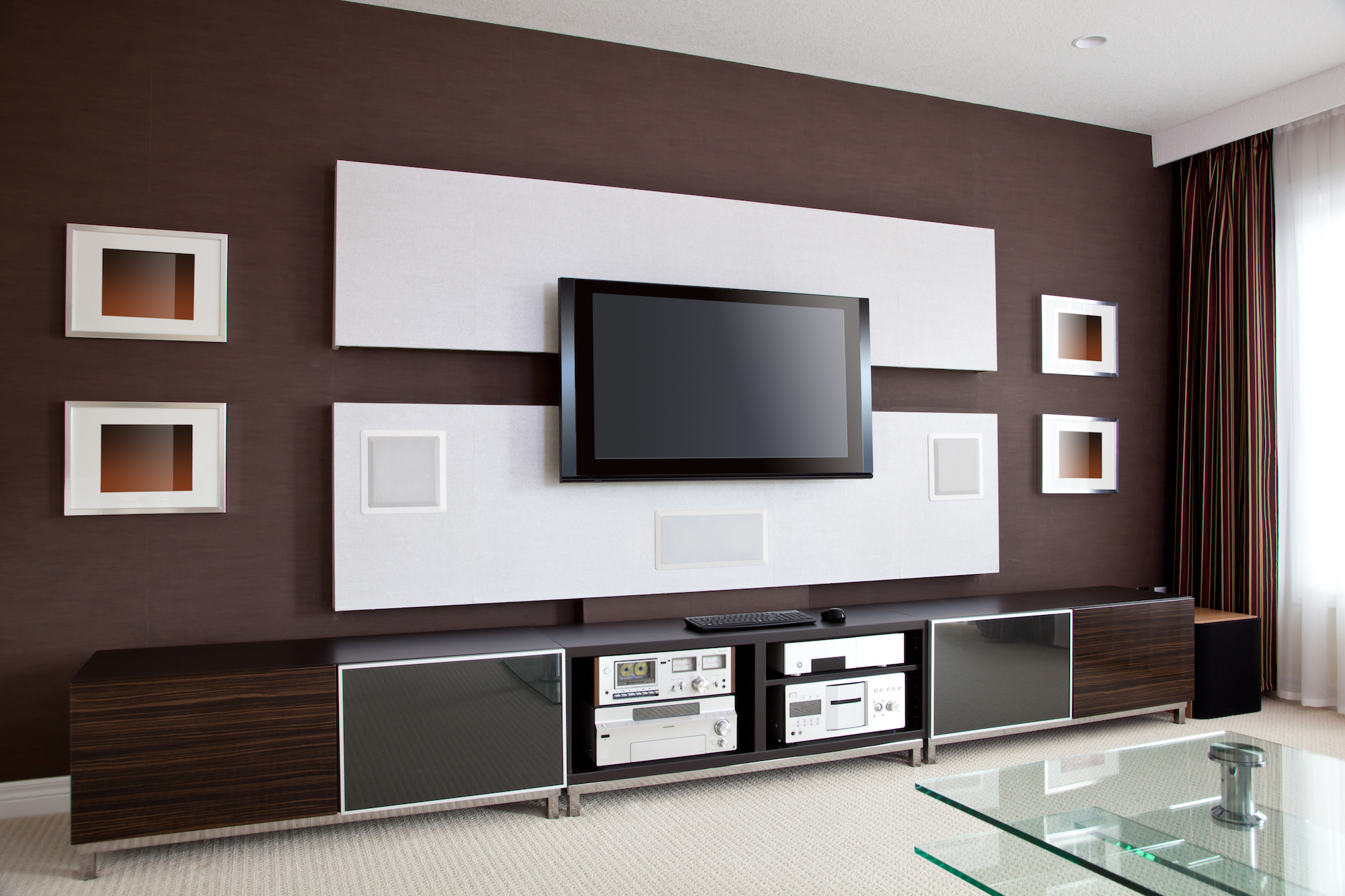 Room with TV mounted on the wall above a cabinet containing stereo equipment.