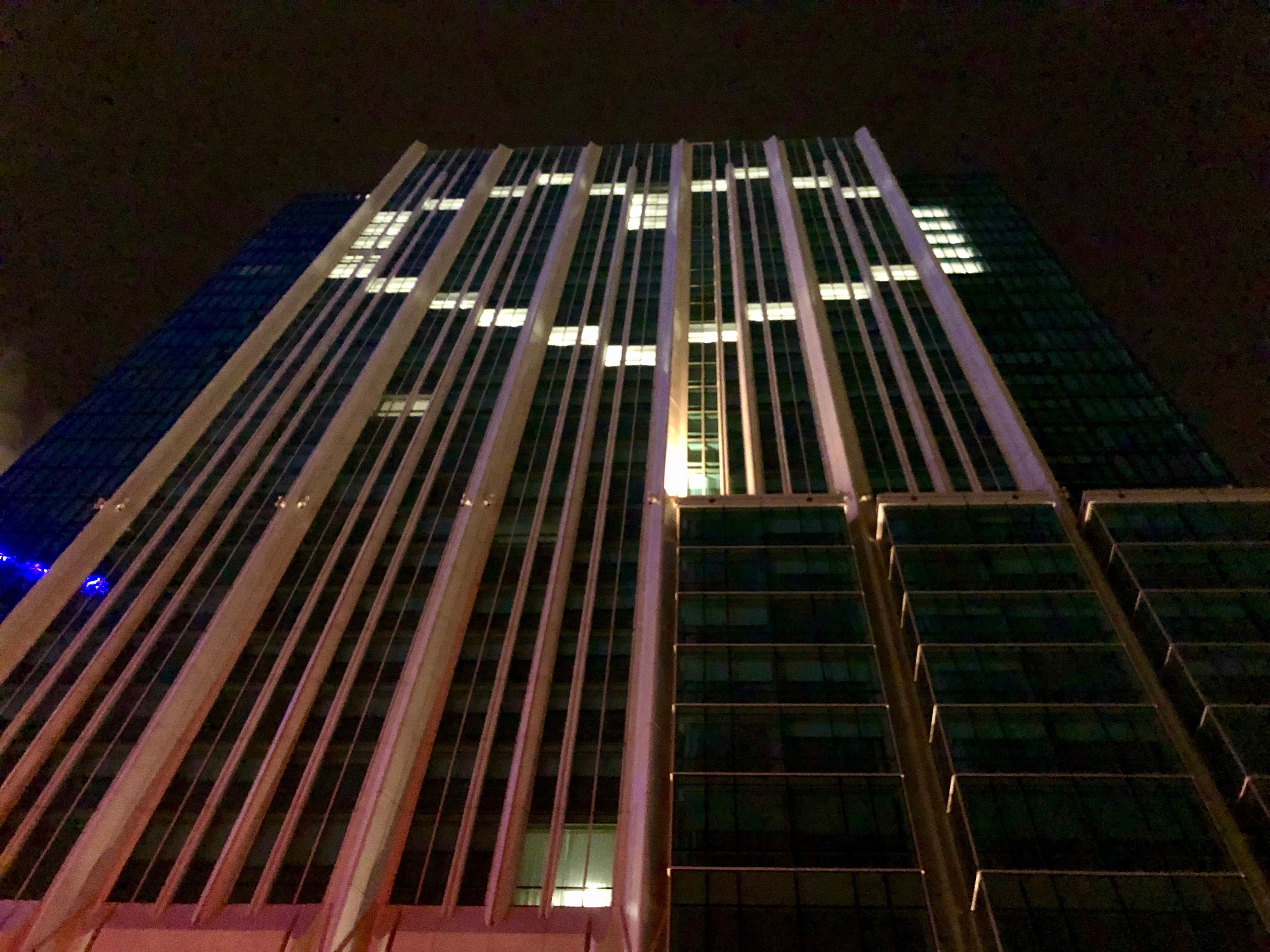 A tall building with its facade windows lit up in the shape of a heart.