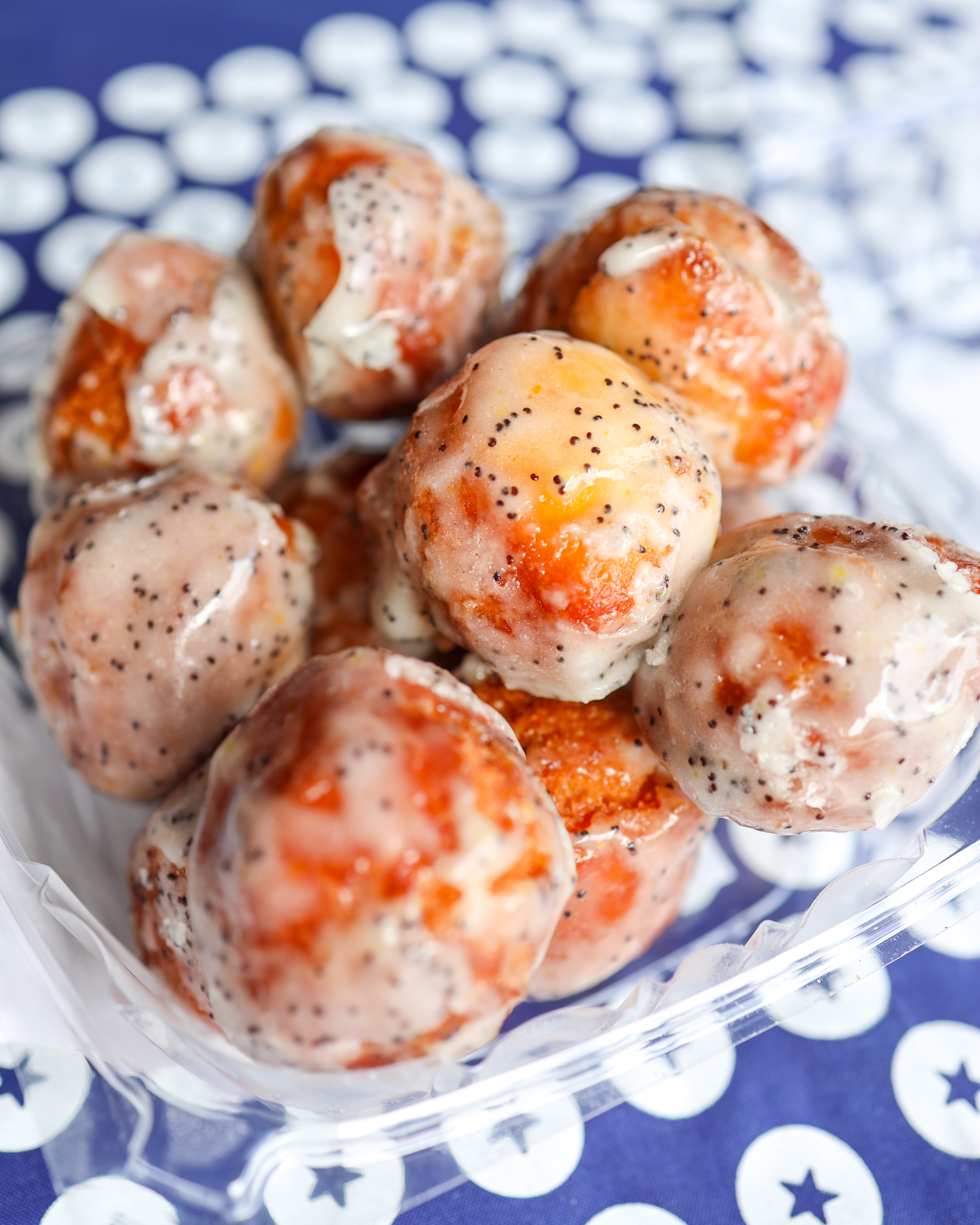 A pile of glazed, poppyseed-dotted doughnut holes sit in a plastic clamshell container. These are Blue Star's buttermilk doughnut holes