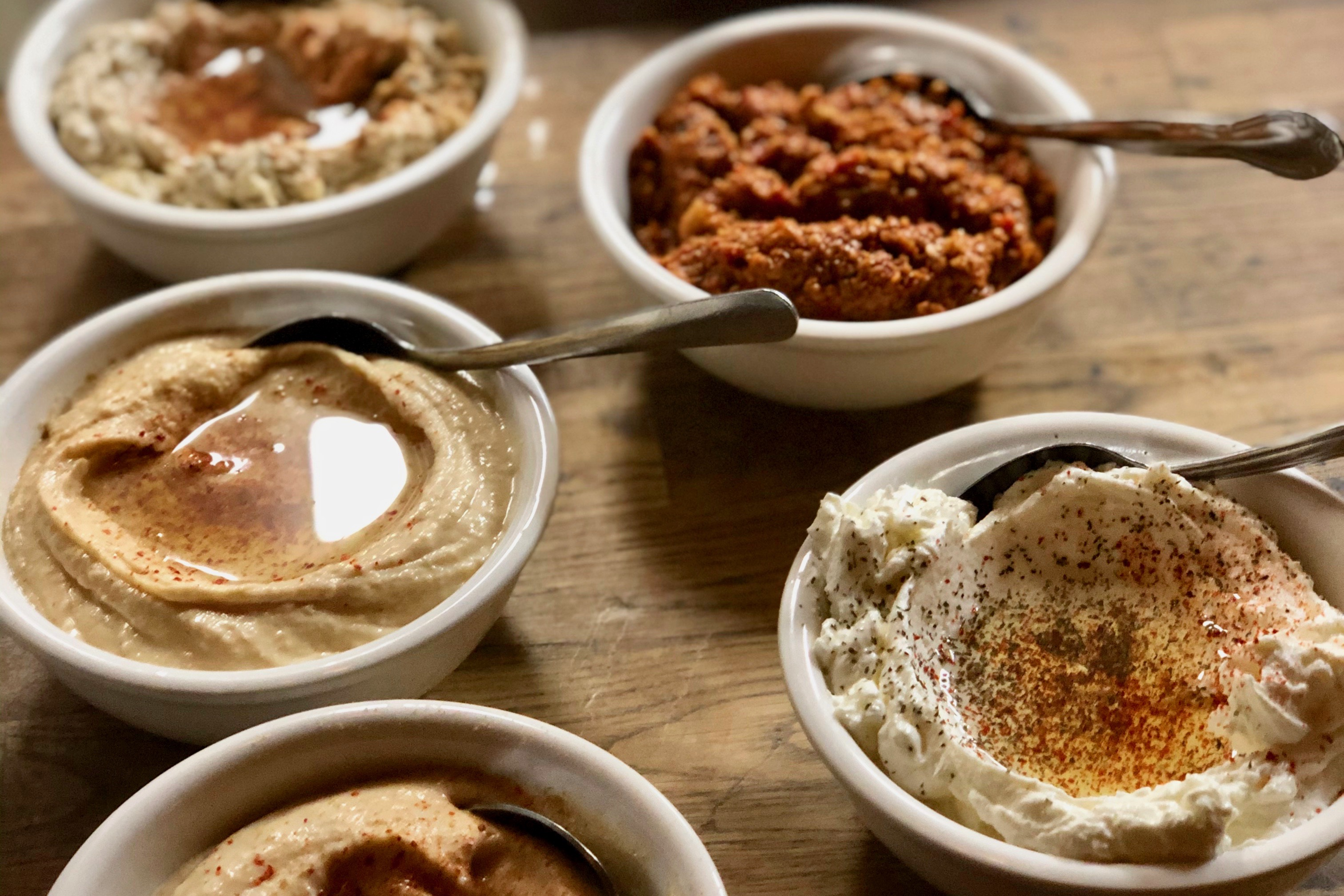 several small bowls of middle eastern dips