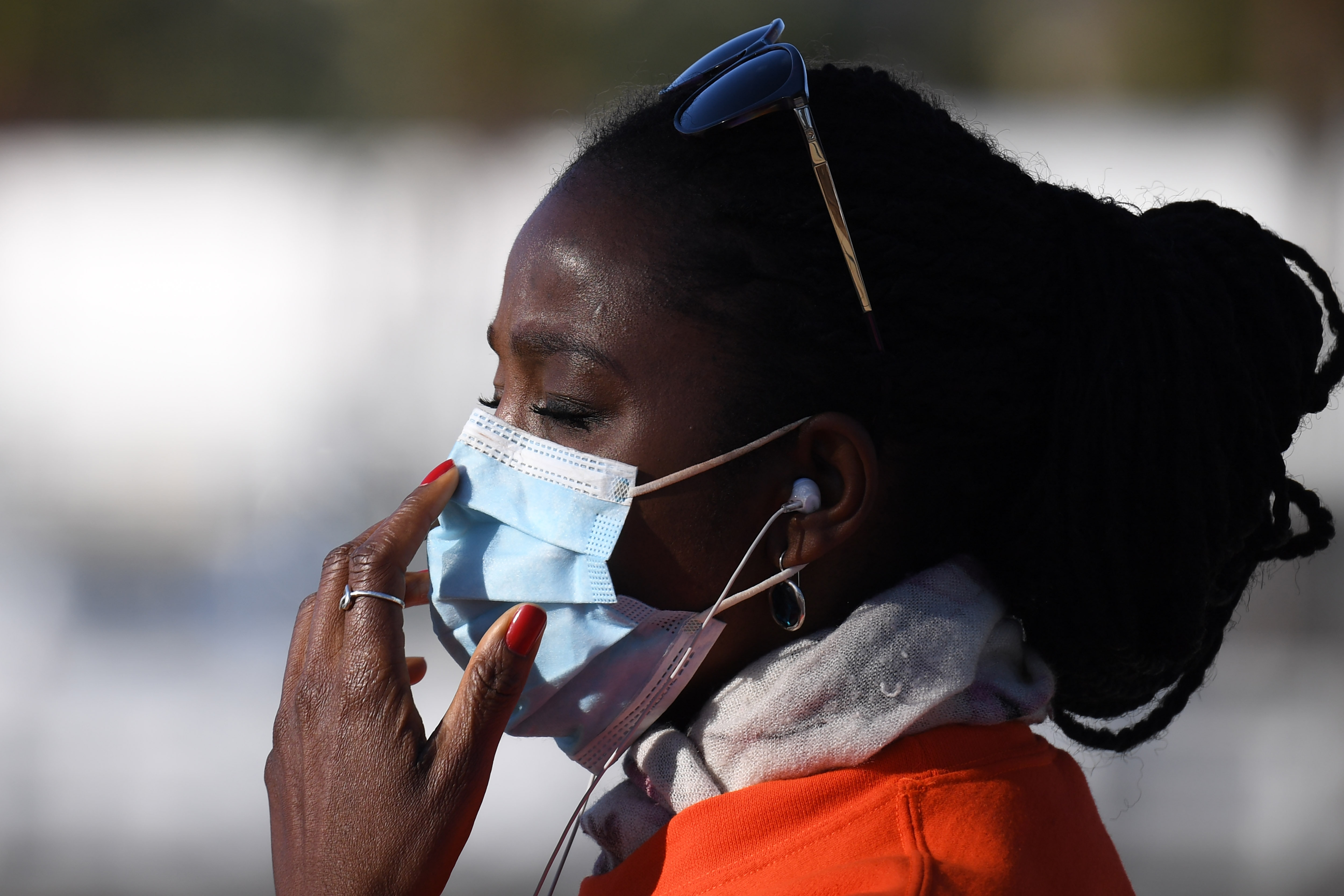 A close up portrait of black woman with braids, sunglasses, and a blue surgical mask. She adjusts the mask slightly, her eyes closed.