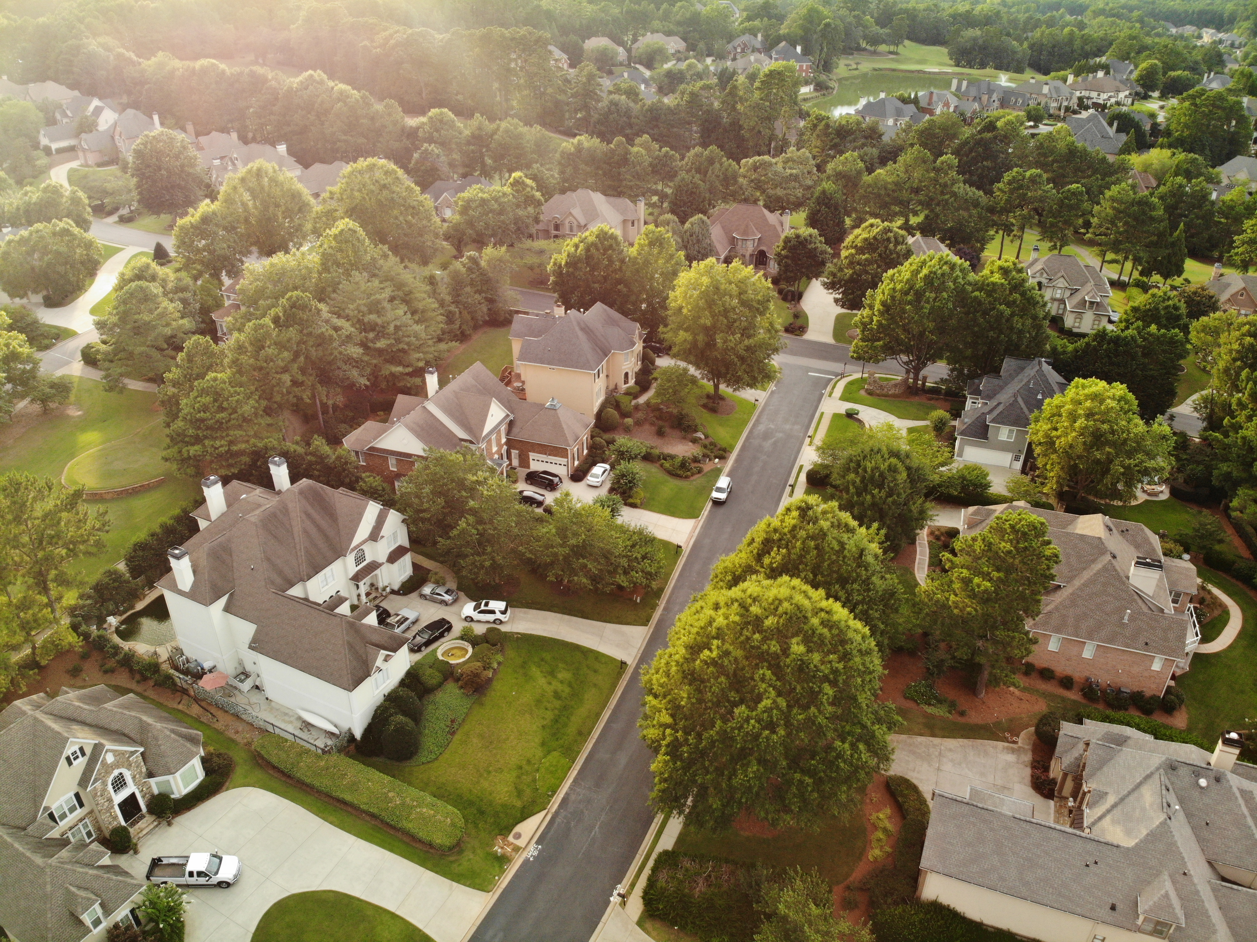 Aerial view of a residential neighborhood, large homes surrounded by big green trees and yards.